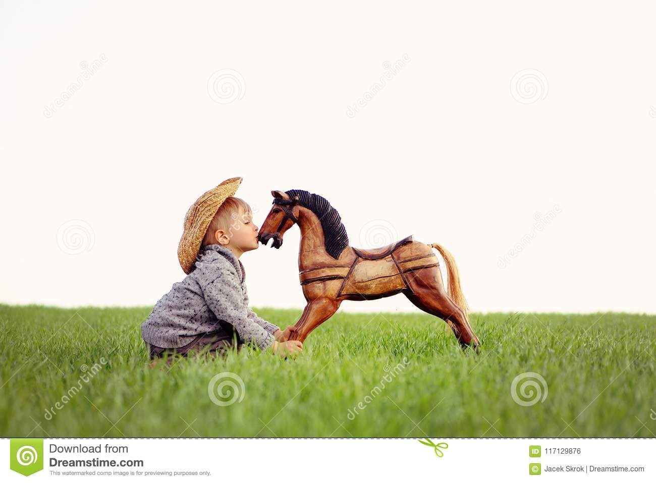 A small child, a boy is kissing a rocking horse on a meadow. Happy childhood in the countryside, the child looks after his pet