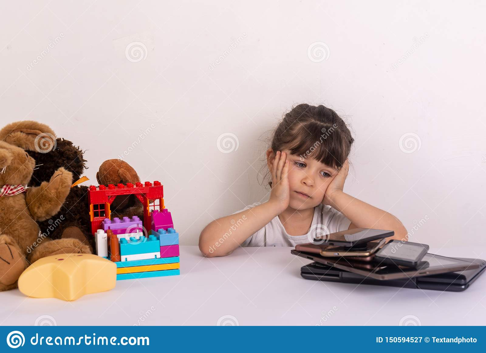 Kid tired because of too much information. Stressed little girl sitting near phones, smartphones, laptops, pc tablets.
