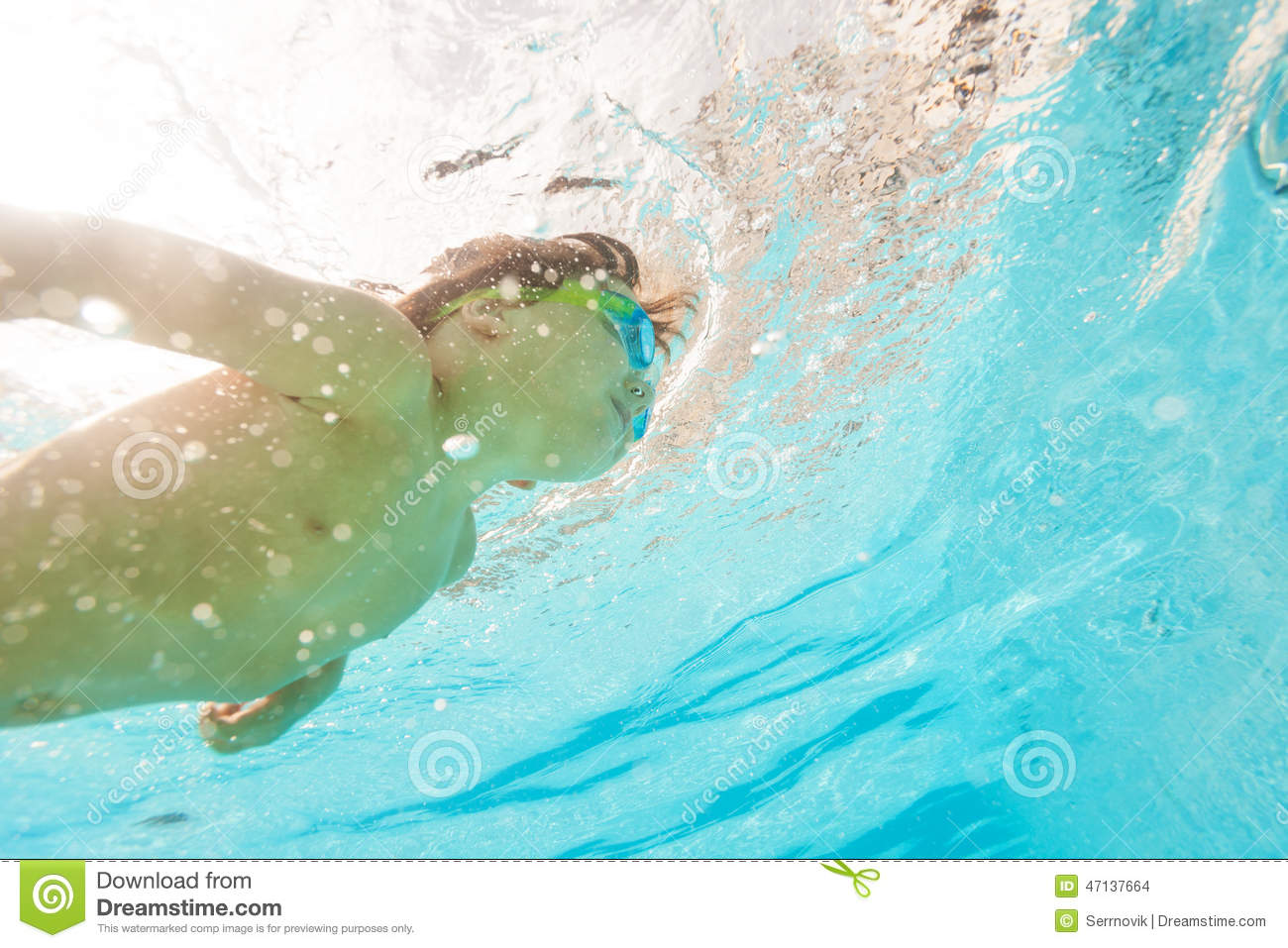 Kid Wearing Goggles Swims Under Water Of Pool