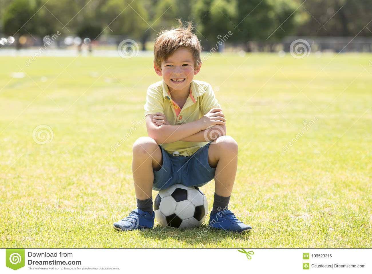 Kid 7 or 8 years old enjoying happy playing football soccer at grass city park field posing smiling proud sitting on the ball in