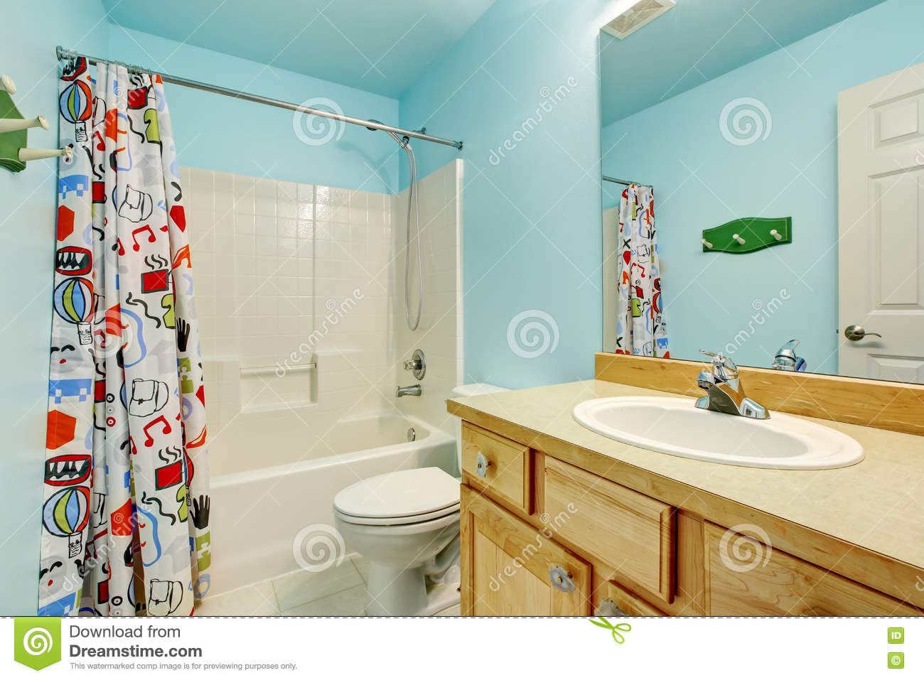 Kids Bathroom In Blue Tones With Wooden Cabinets And Colorful Shower Curtain