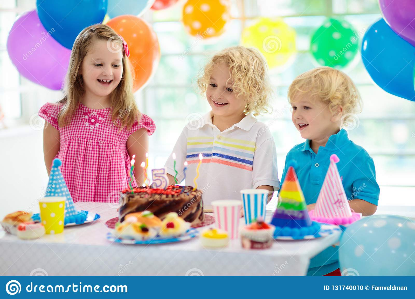 Kids birthday party. Child blowing out candles on colorful cake. Decorated home with rainbow flag banners, balloons. Farm animals