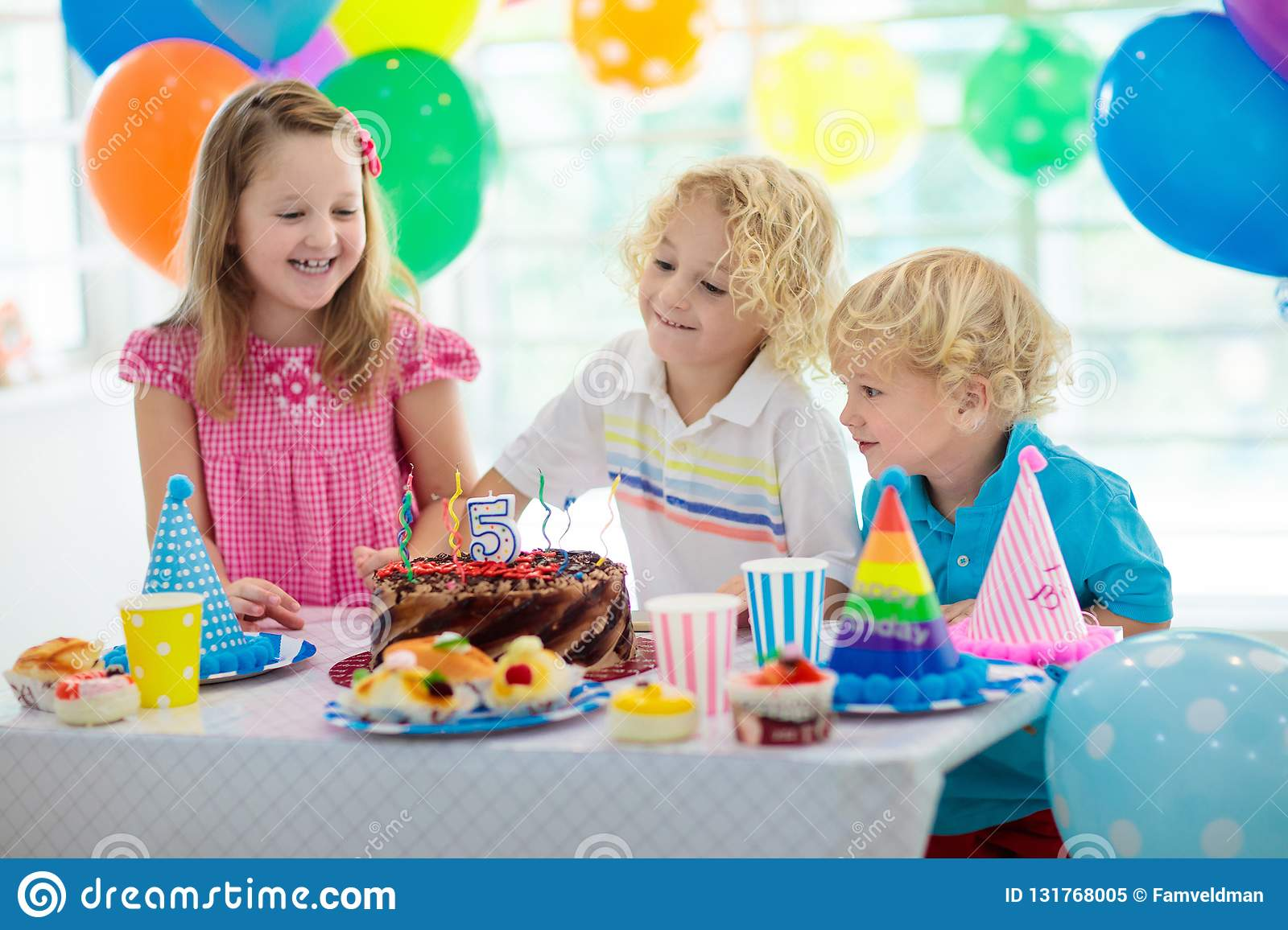 Kids Birthday Party Child Blowing Out Candles On Colorful Cake Decorated Home With Rainbow Flag Banners Balloons Farm Animals Theme Celebration