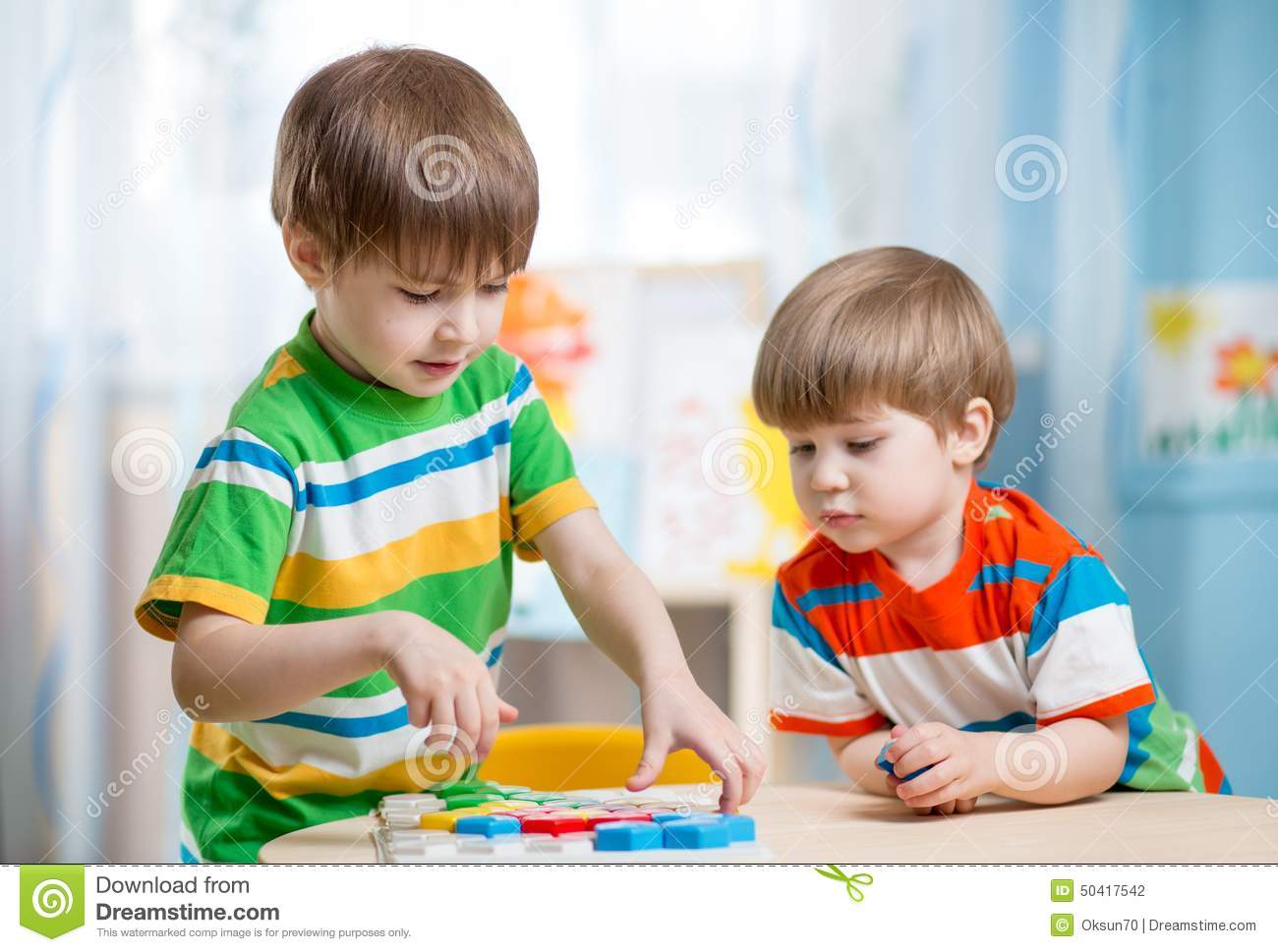 Kids Brothers Playing Together At Table Stock Photo