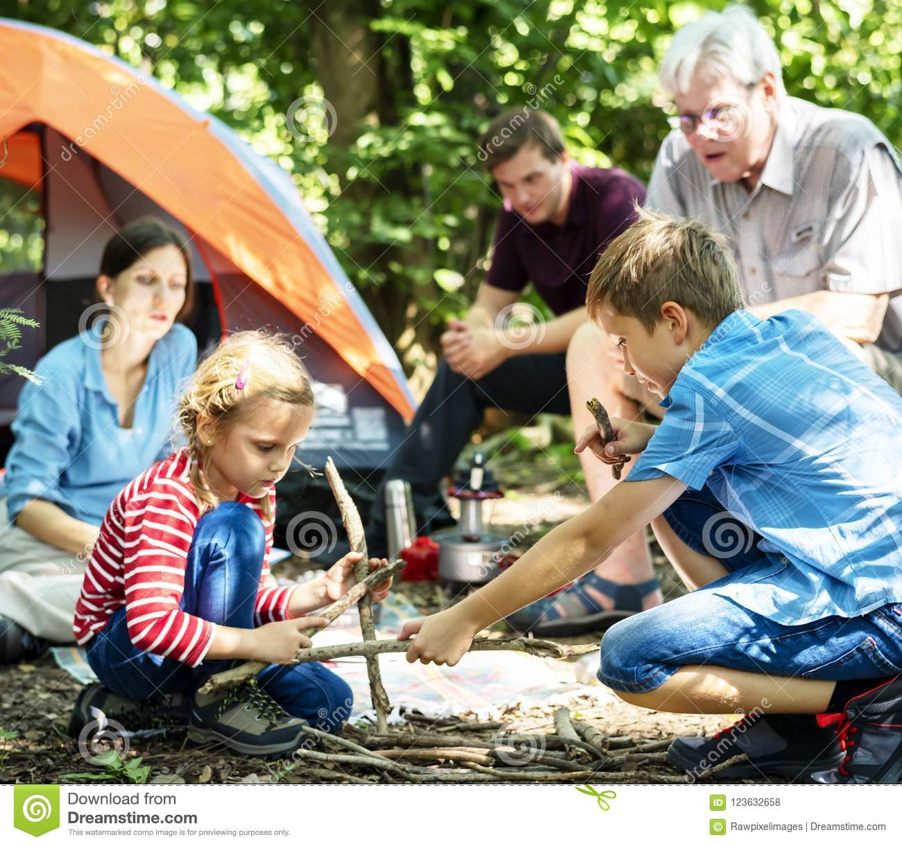 kids building a camp fire in family camping trip stock photo image
