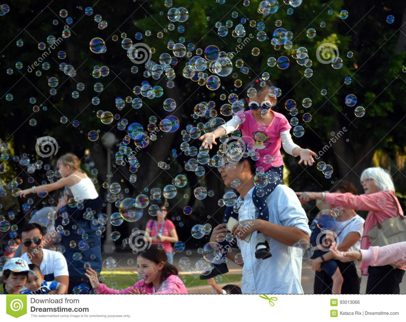Kids catching and having fun and with soap bubbles