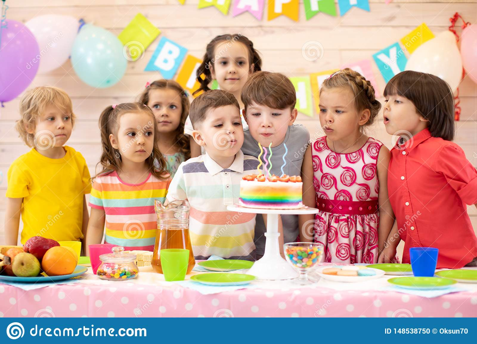 Kids celebrate birthday party and blow candles on festive cake
