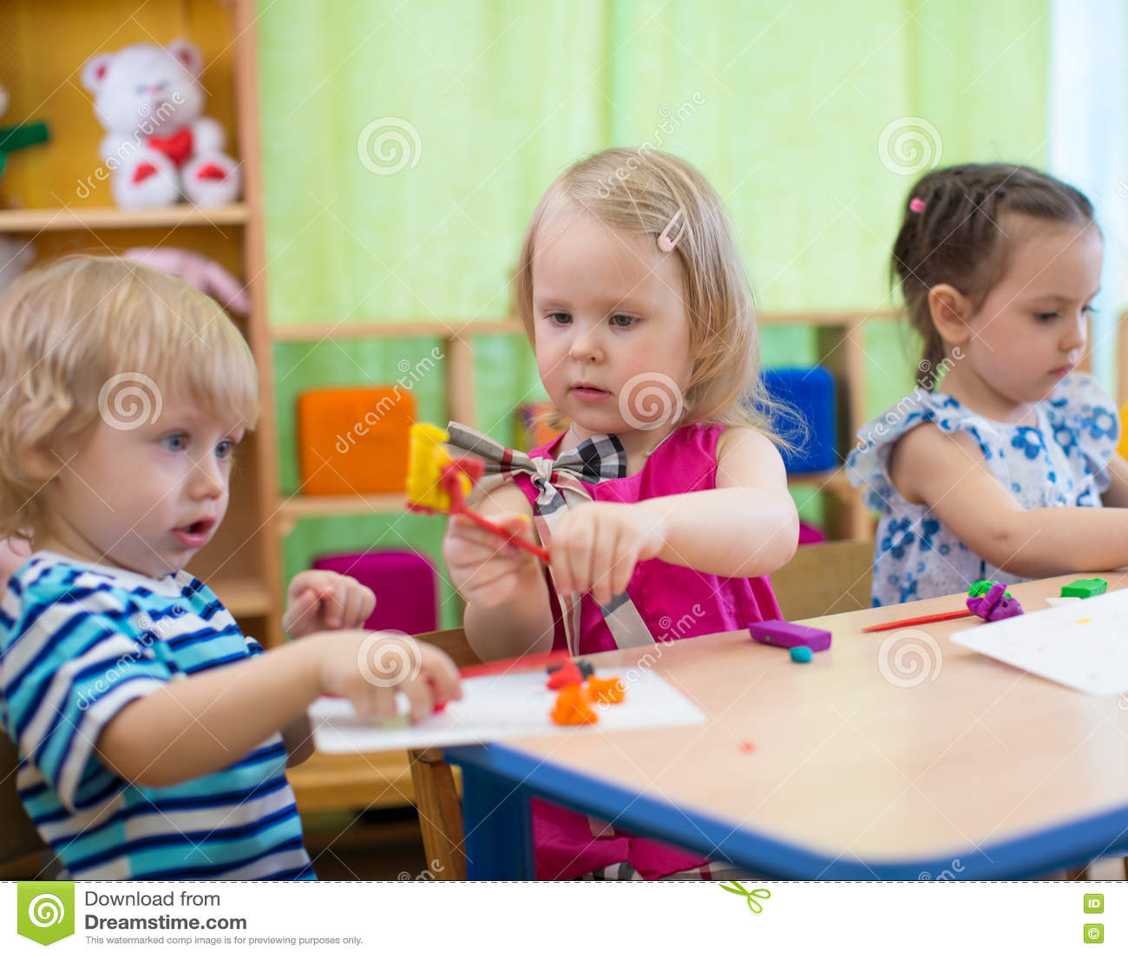 Kids Or Children Creating Arts And Crafts In Kindergarten Girl Is