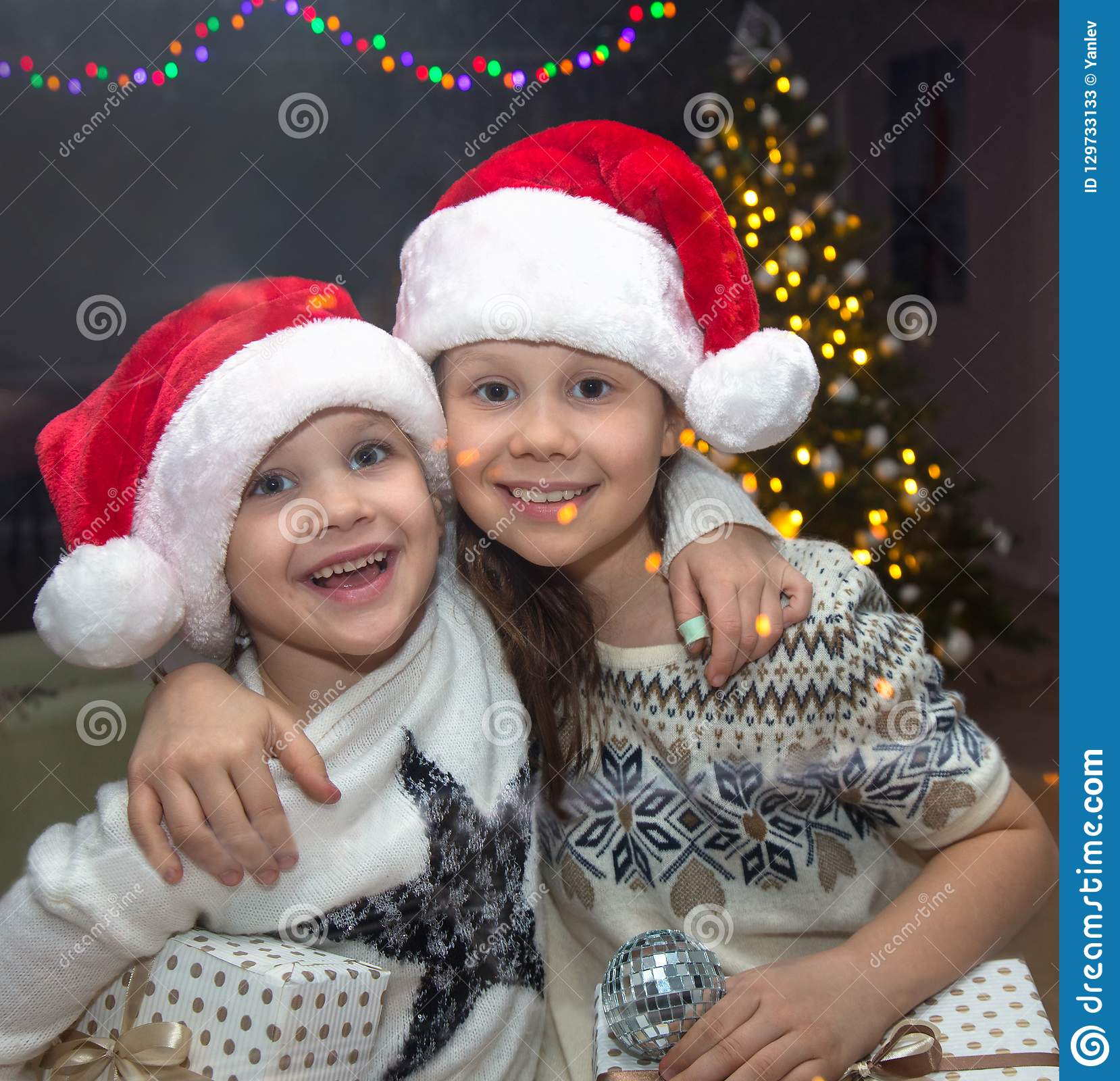 c9a847b89b253 Portrait of Two little girls in the Santa hat with Christmas present under  the Christmas tree