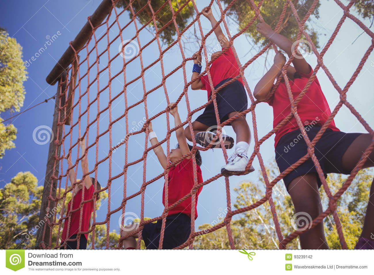 kids climbing a net during obstacle course training stock photo