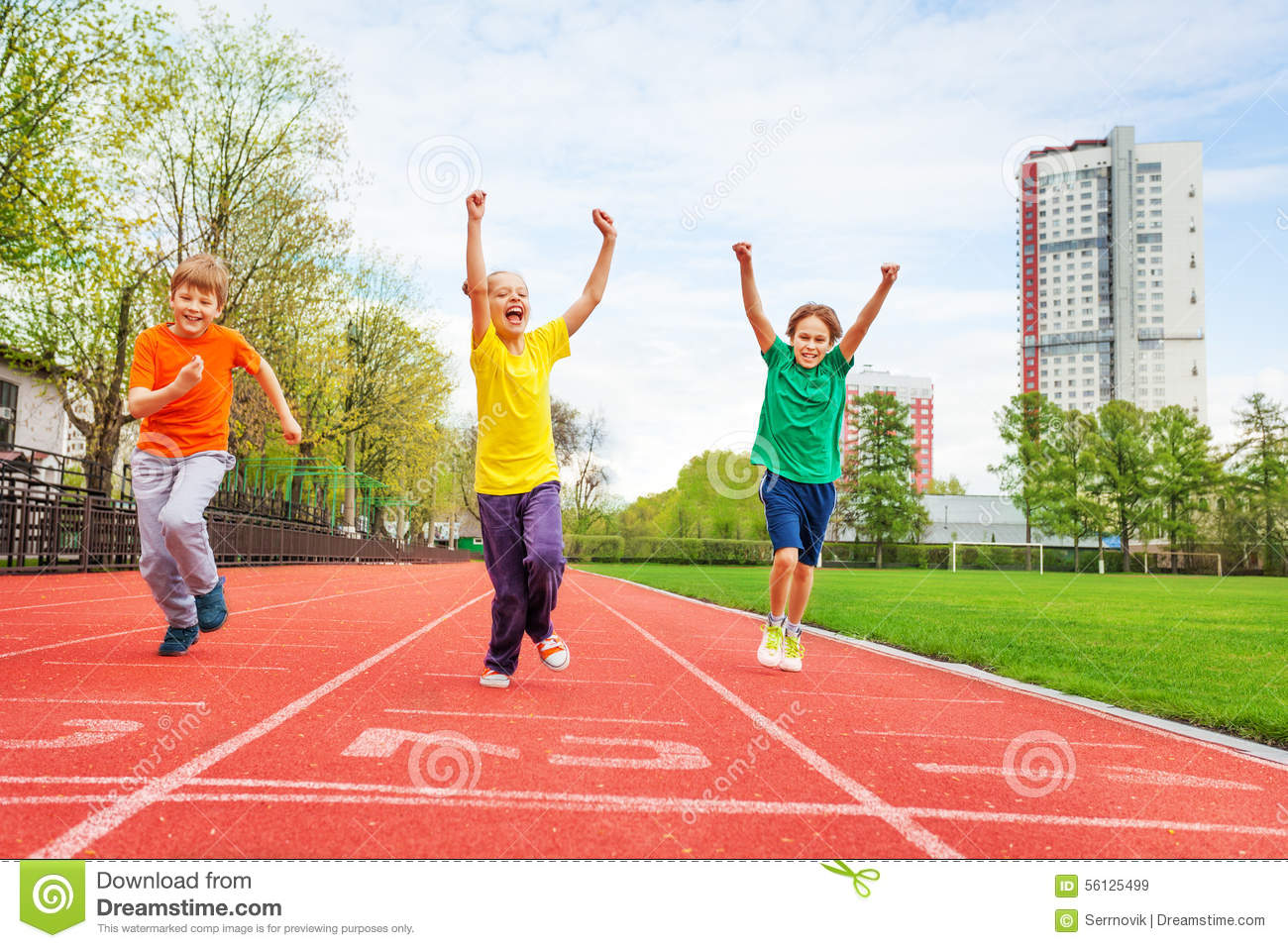 Kids in colorful uniforms with arms up running
