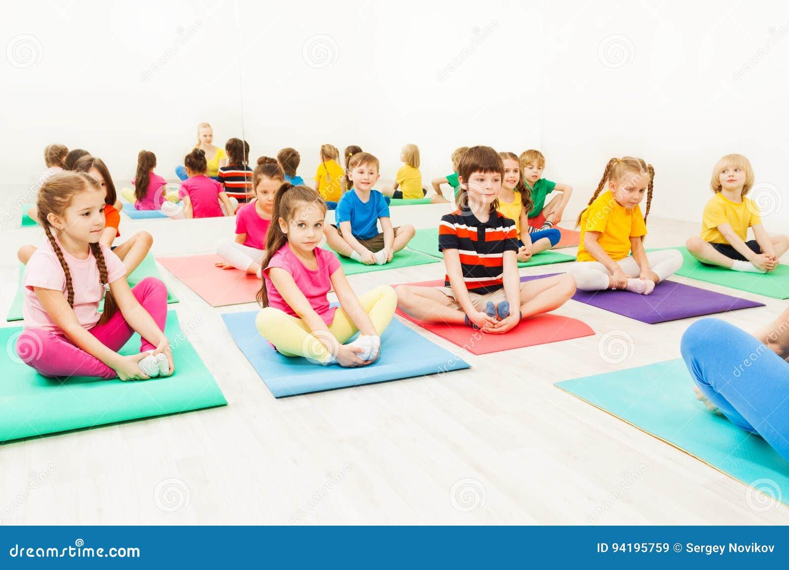 Kids Doing Butterfly Exercise Sitting On Yoga Mats Stock