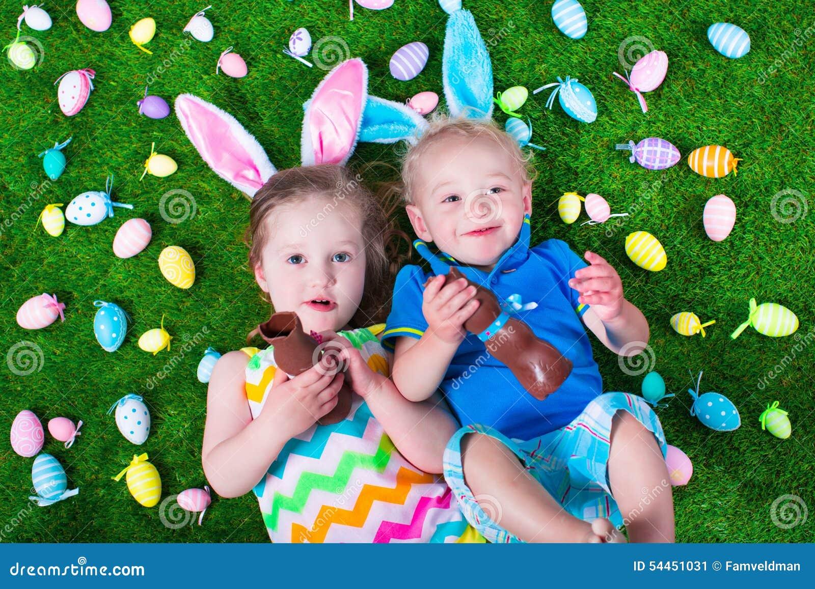 Kids Eating Chocolate Rabbit On Easter Egg Hunt Stock