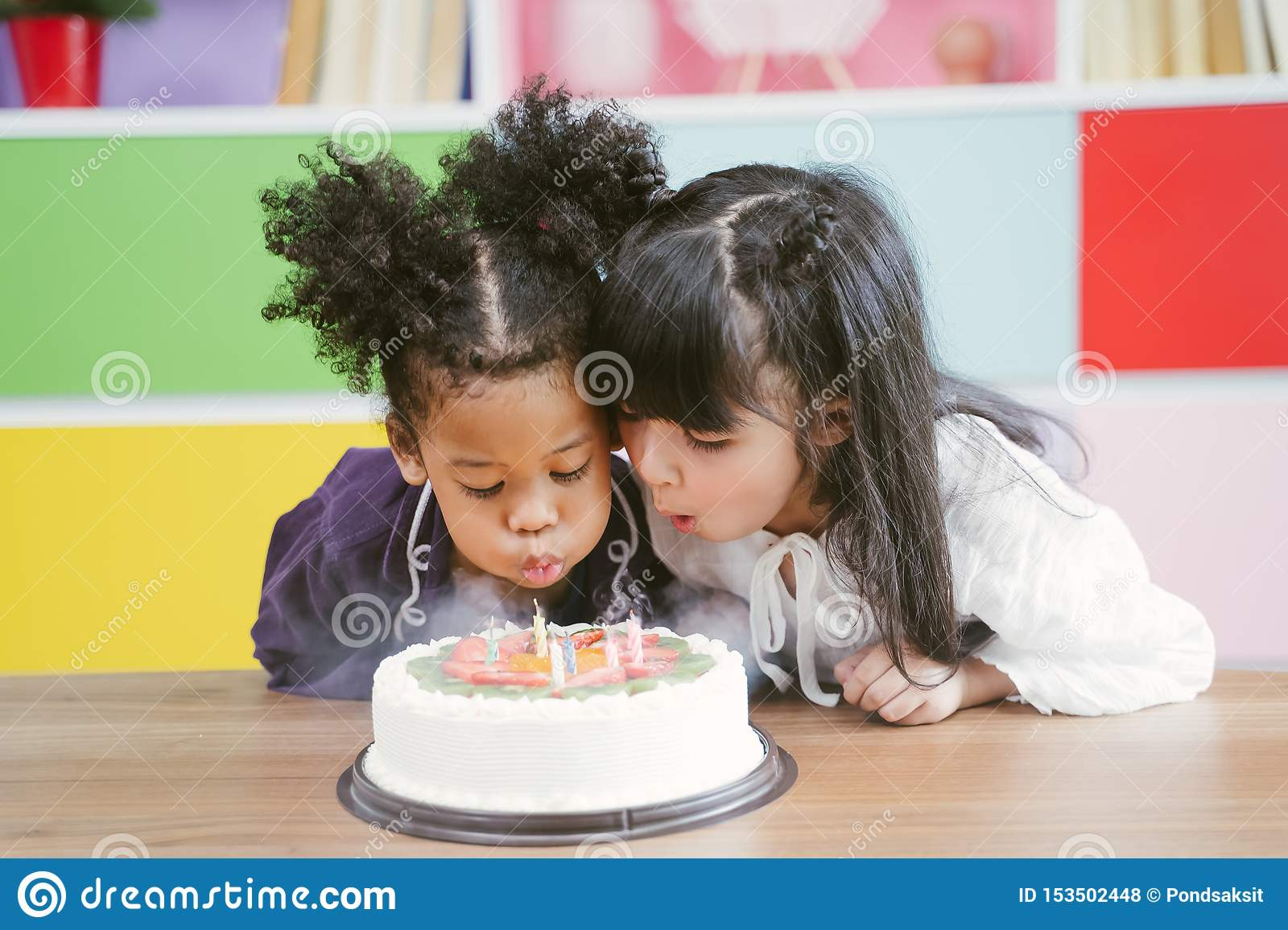 Kids enjoying a birthday party blowing out the candle on cake.