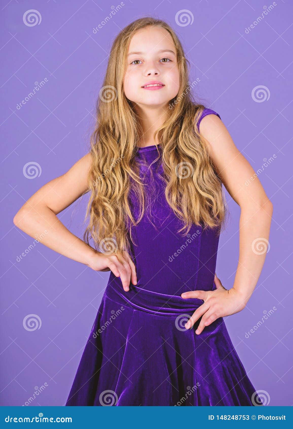 Kids fashion. Girl cute child wear velvet violet dress. Clothes for ballroom dance. Kid fashionable dress looks adorable