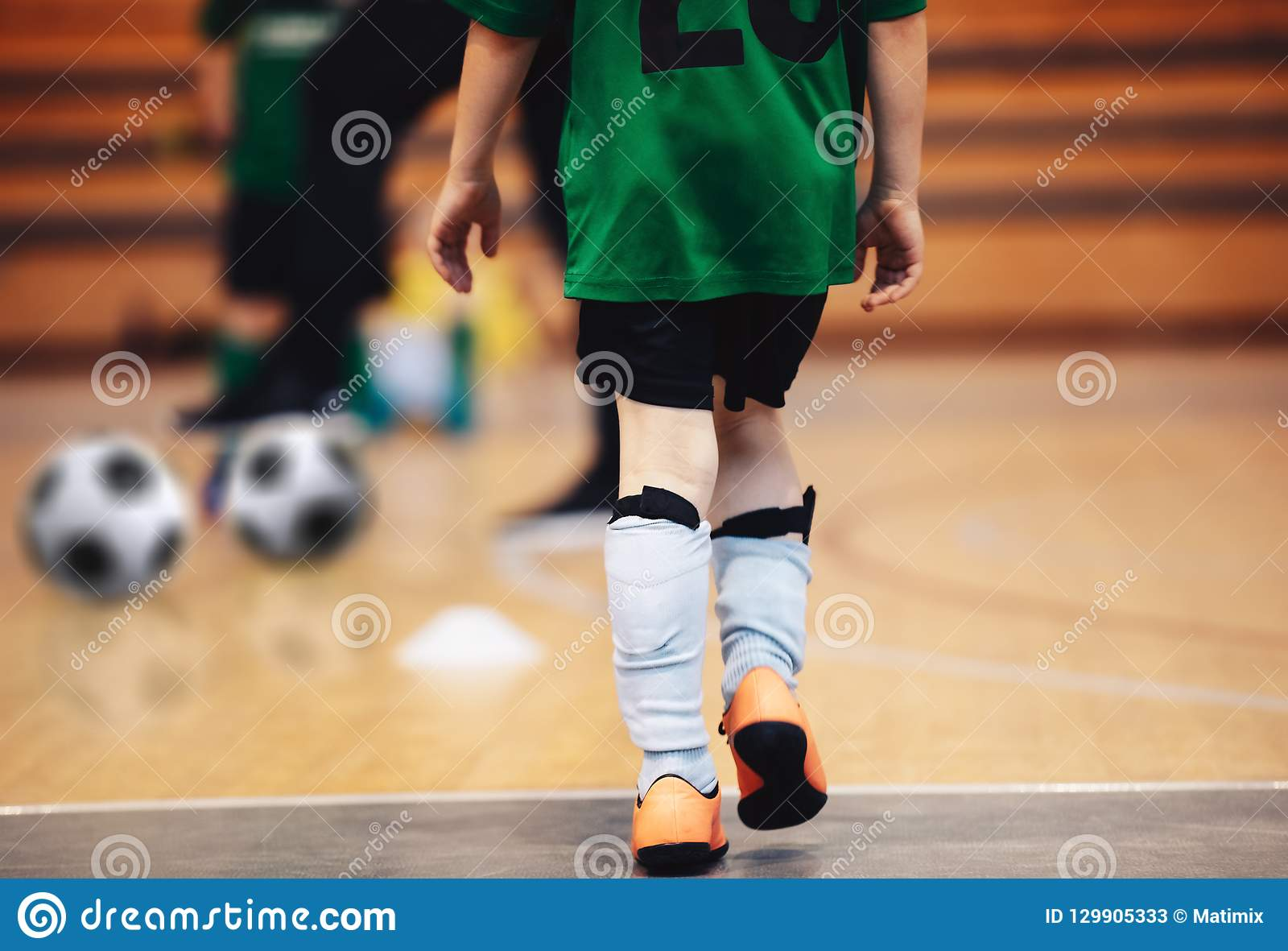 Kids futsal training. Indoor soccer players training with balls.