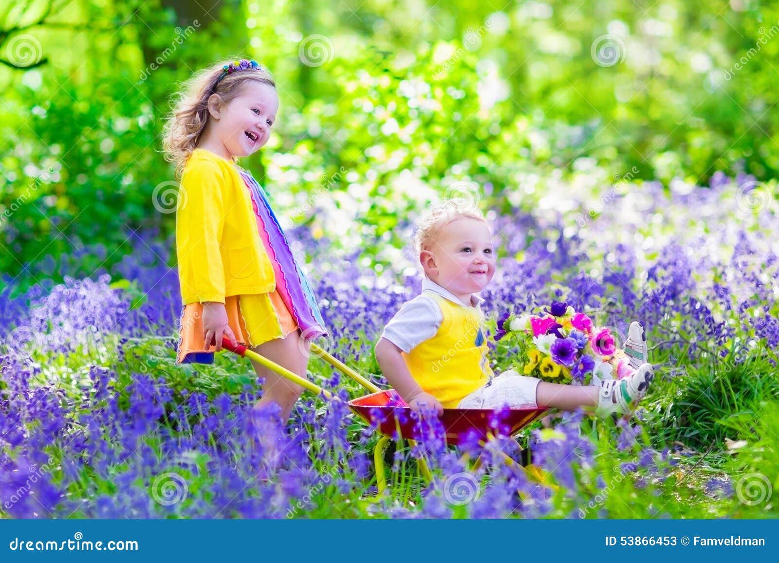 Garden planting flowers watering flower bed child pushing wheel