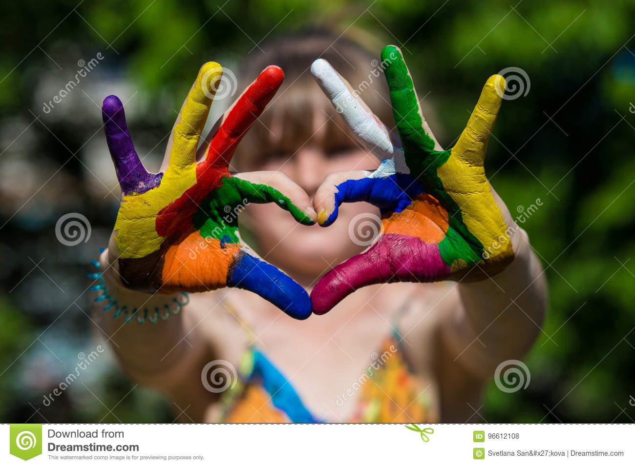 Kids hands in color paints make a heart shape, focus on hands