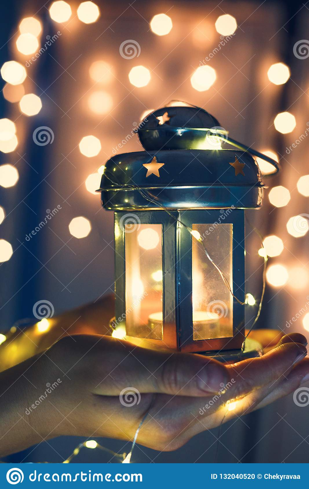 Kids holds Christmas lantern in hands on lights bokeh background.