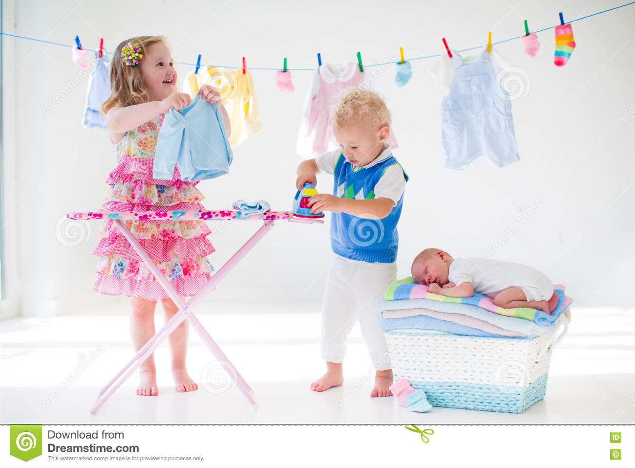 kids ironing clothes for baby brother royaltyfree stock