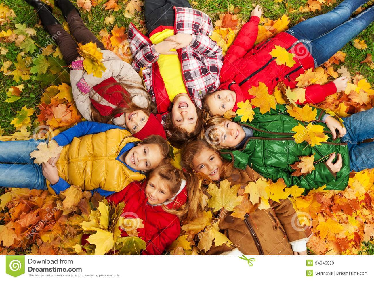 Large group of kids laying in the grass with maple leaves all over