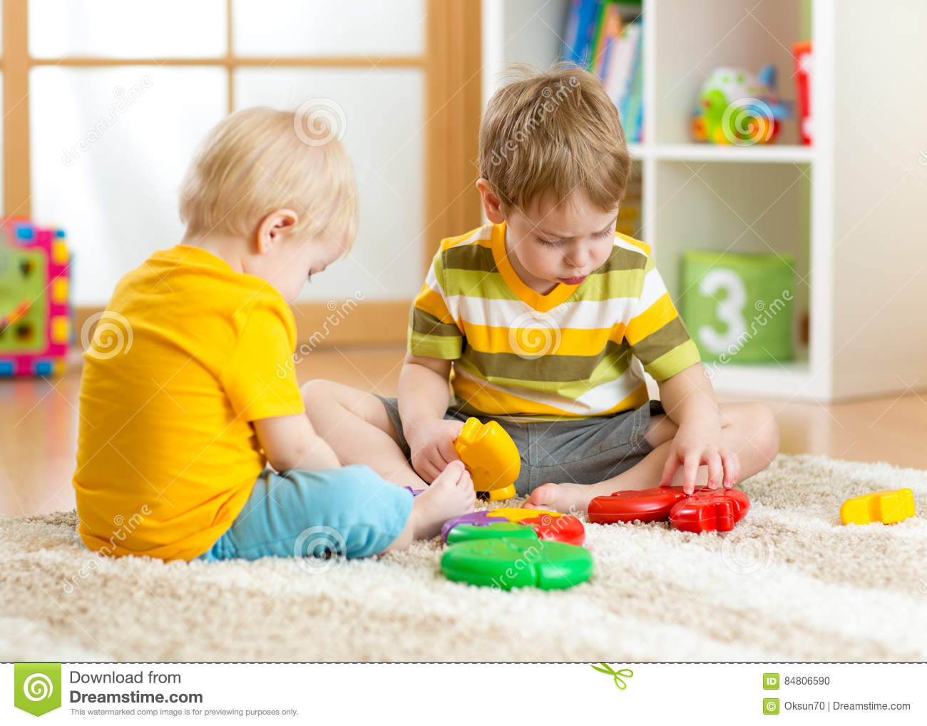 Kids little boy plays with a multi colored puzzle in nursery