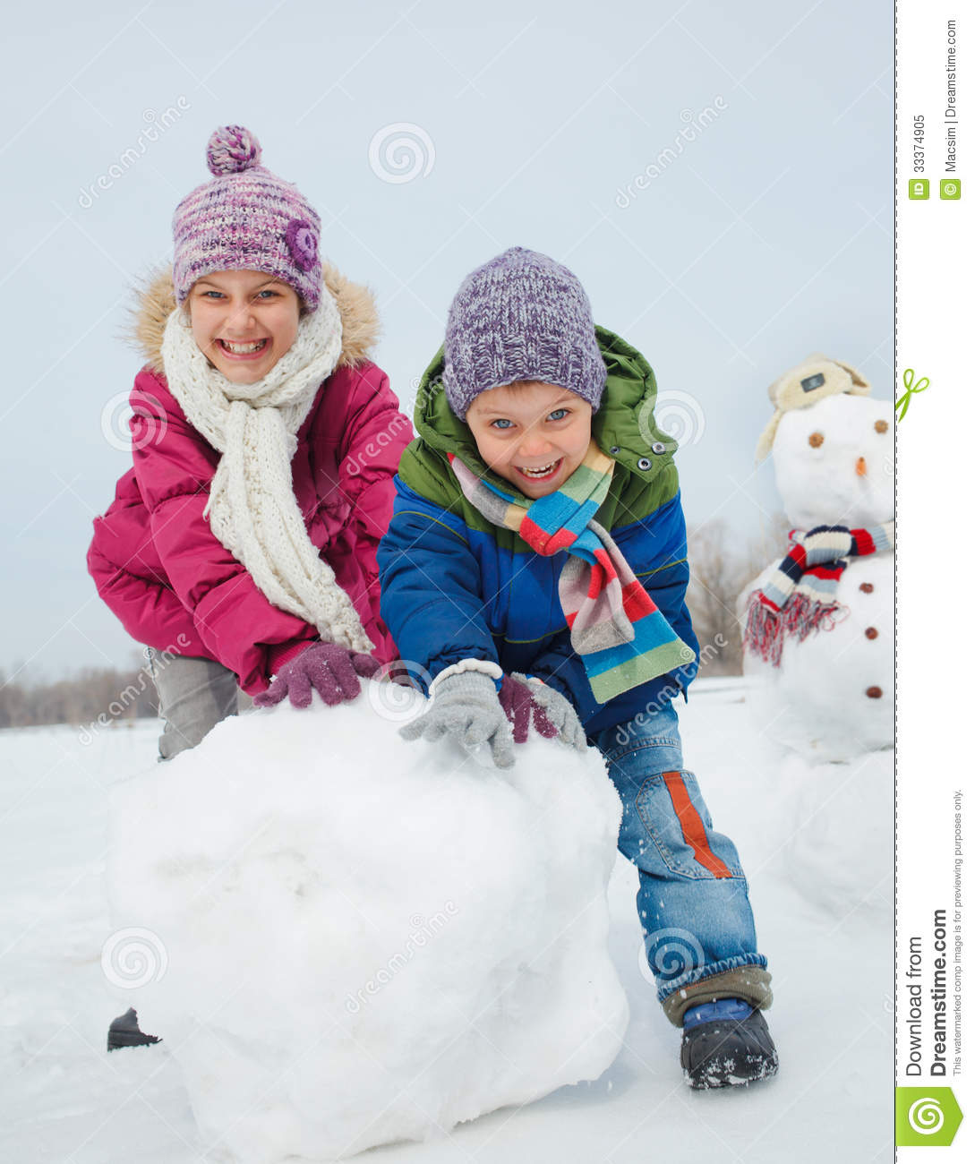 Happy beautiful children building snowman outside in winter time.