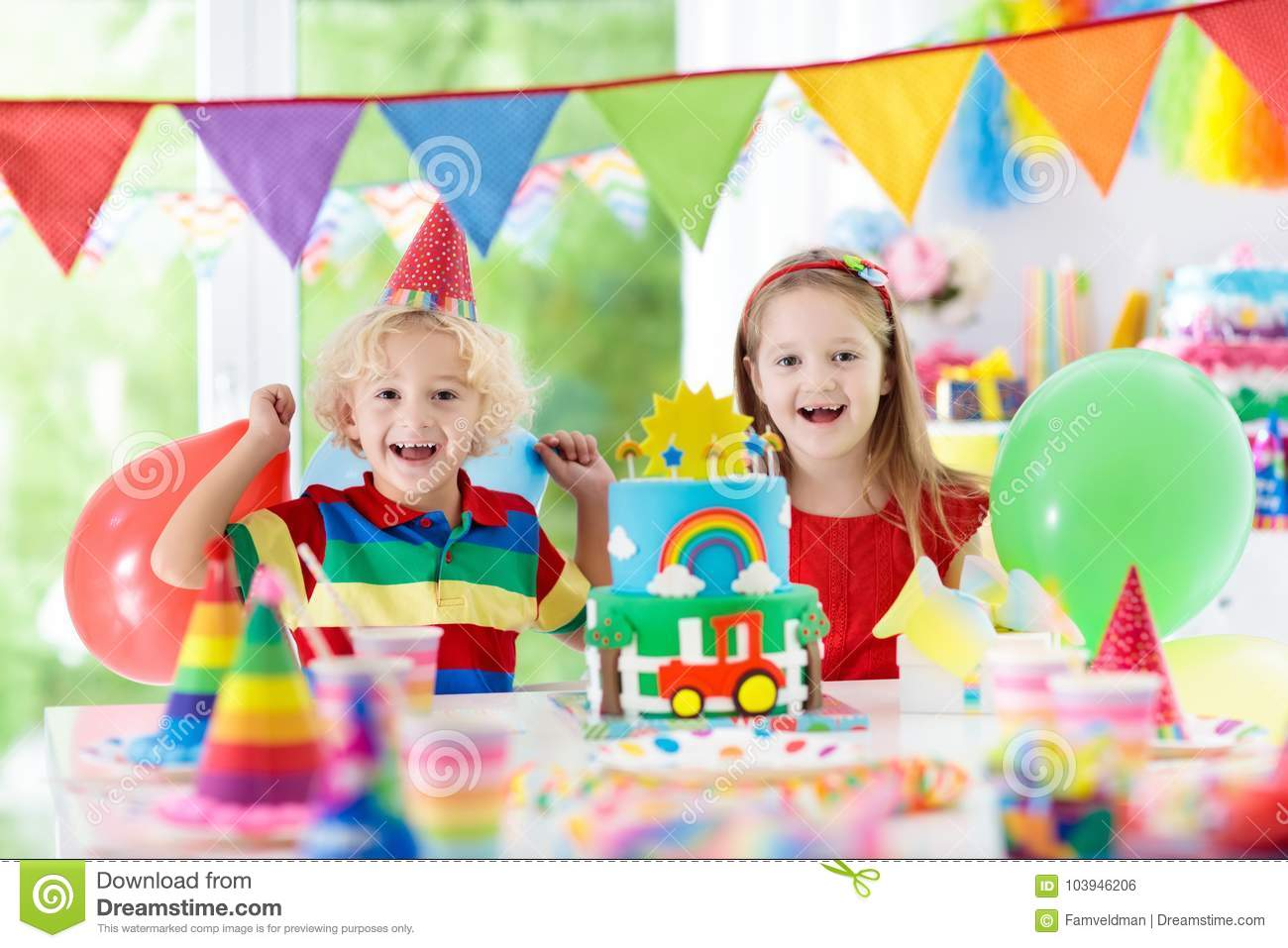 Kids Birthday Party Child Blowing Out Candles On Colorful Cake Decorated Home With Rainbow Flag Banners Balloons Confetti Farm And Transport Theme