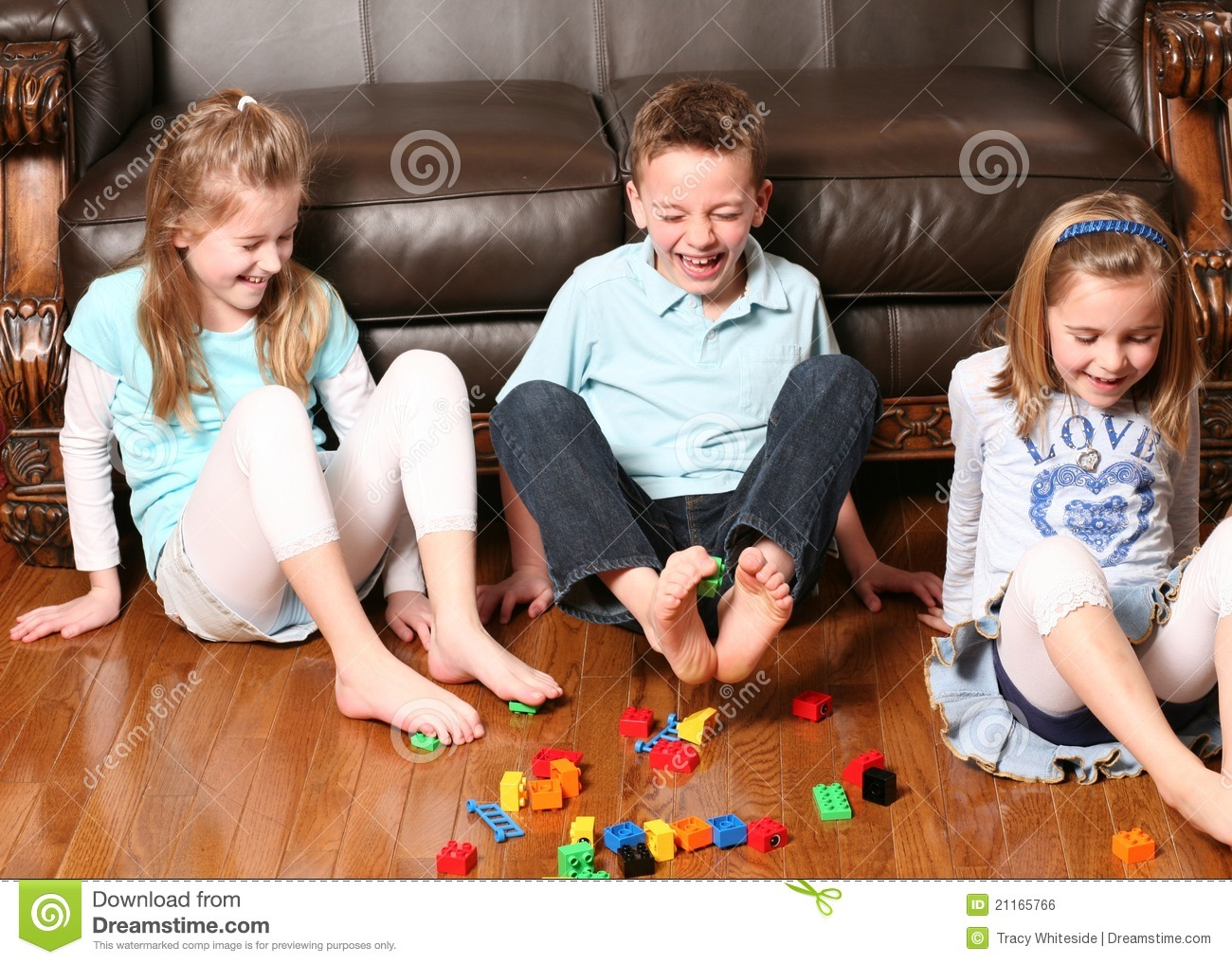 Three childrens playing with blocks with their feet.