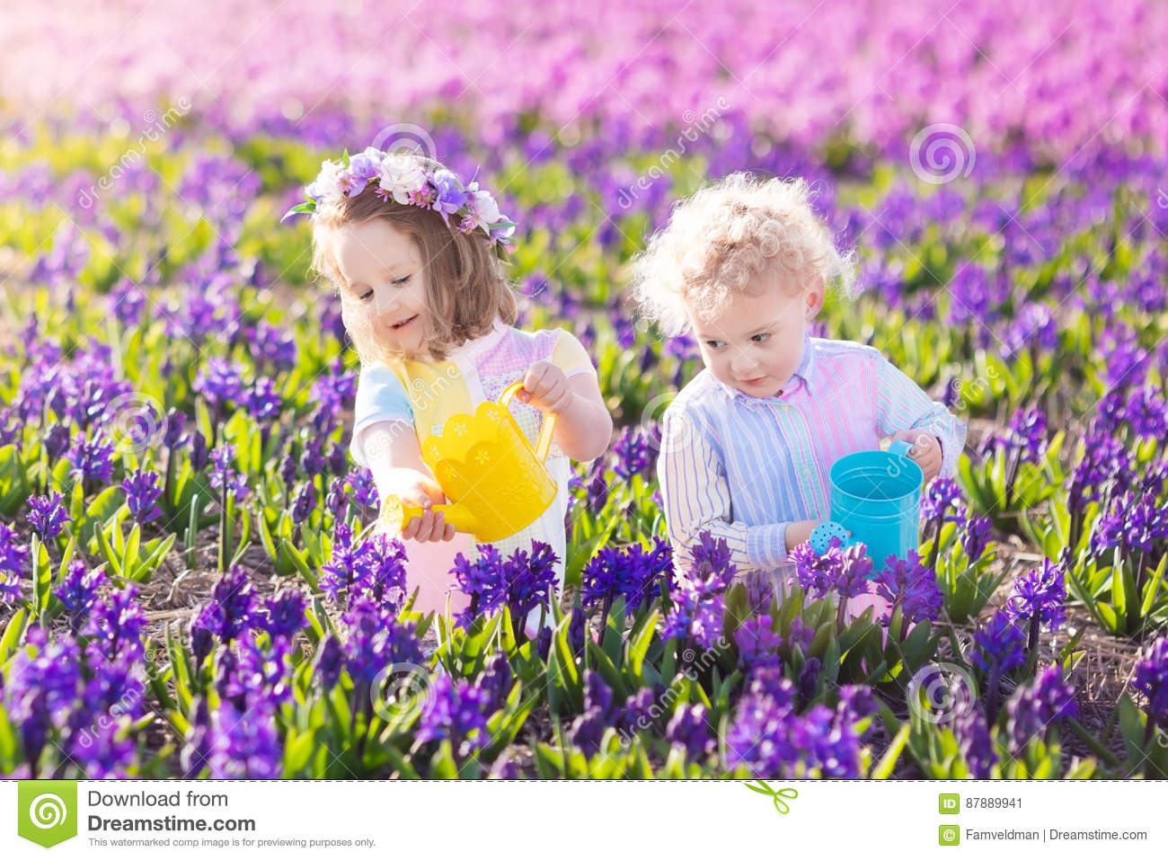 Kids plant and water flowers in spring garden stock image image of children planting spring flowers in sunny garden little boy and girl gardener plant hyacinth daffodil snowdrop in flower bed gardening tools and water mightylinksfo