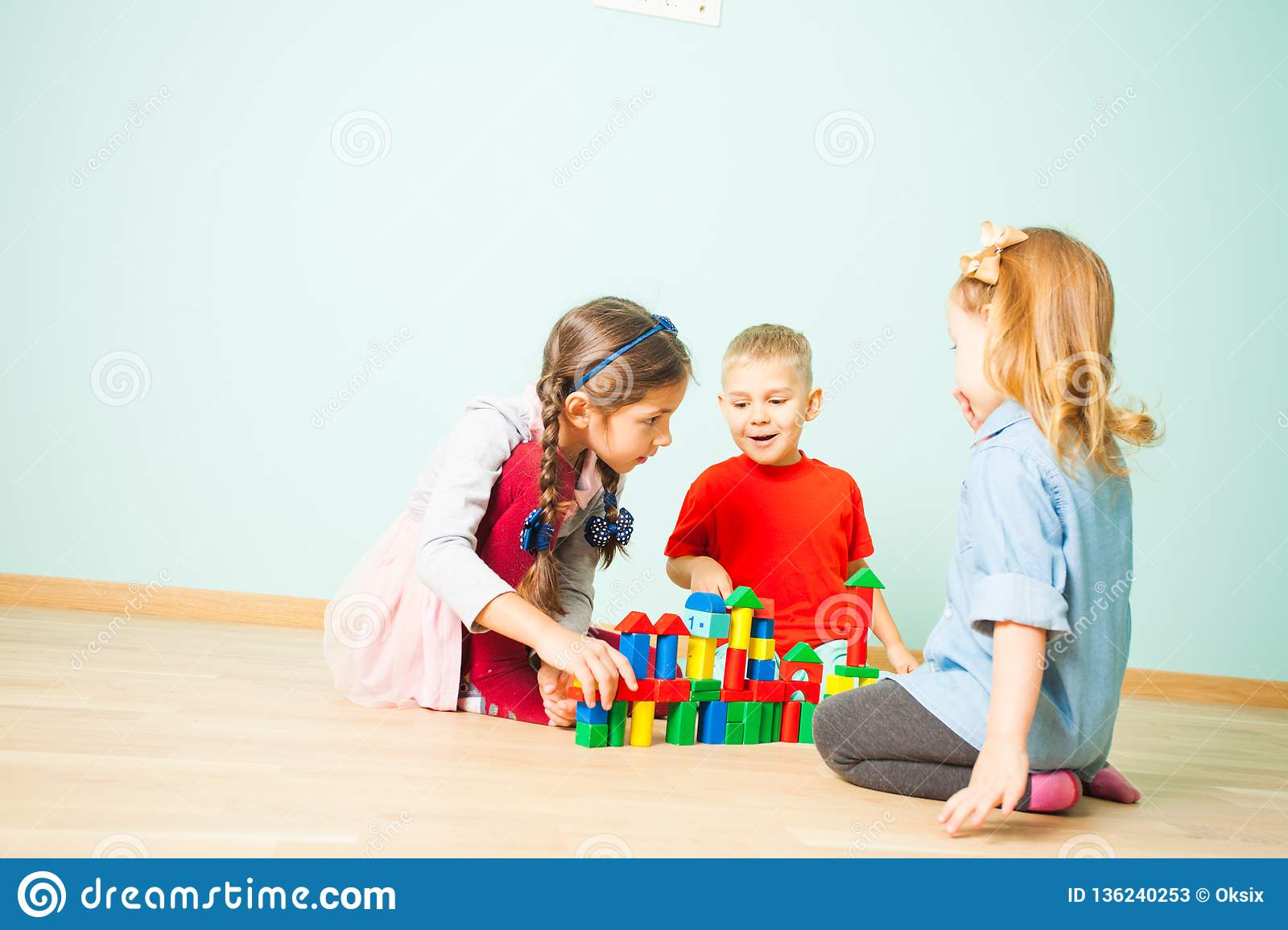 Kids play at day care. Three preschoolers building tower from wooden cubes