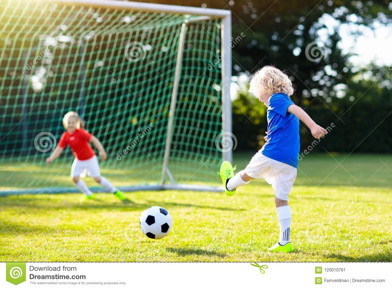 282f5e7c5 Children score a goal during soccer game. Little boy kicking ball. Running  child in team jersey and cleats. School football club. Sports training for  young ...