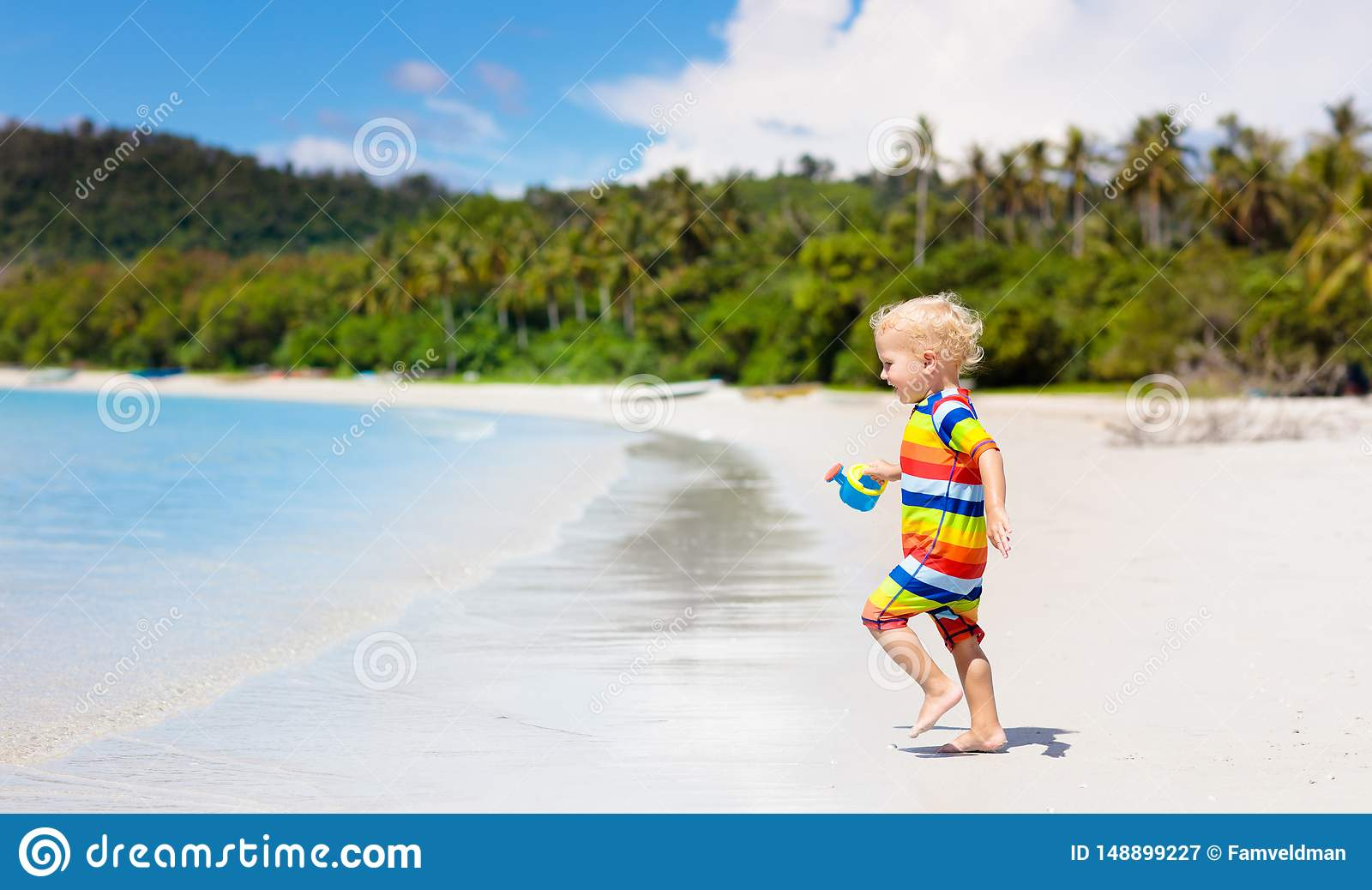 Kids play on tropical beach. Sand and water toy