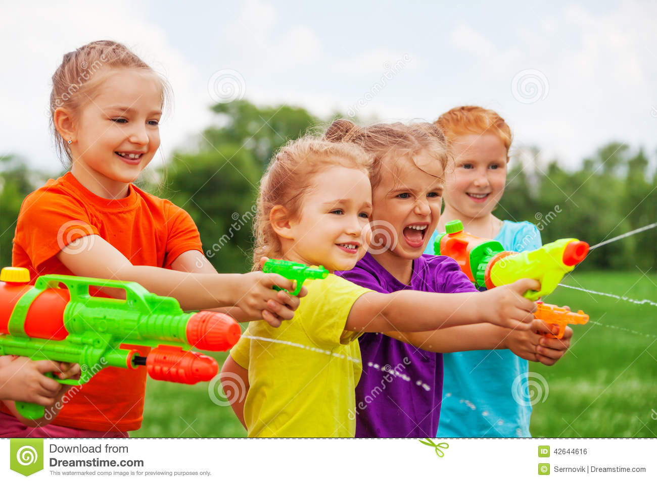 kids play water Kids play with water guns on a meadow Royalty Free Stock Image