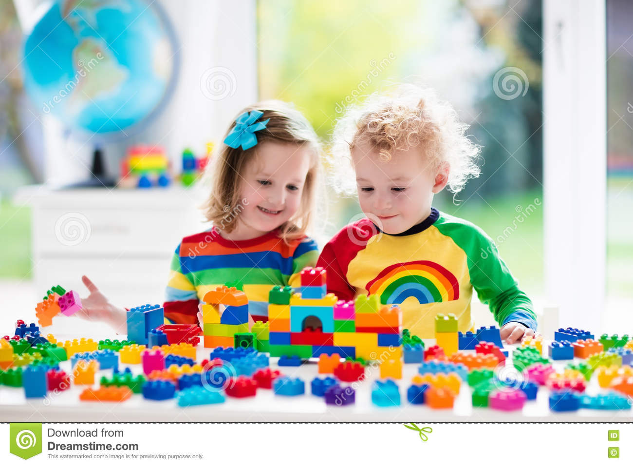Kinder Garden: Kids Playing With Colorful Plastic Blocks Stock Photo