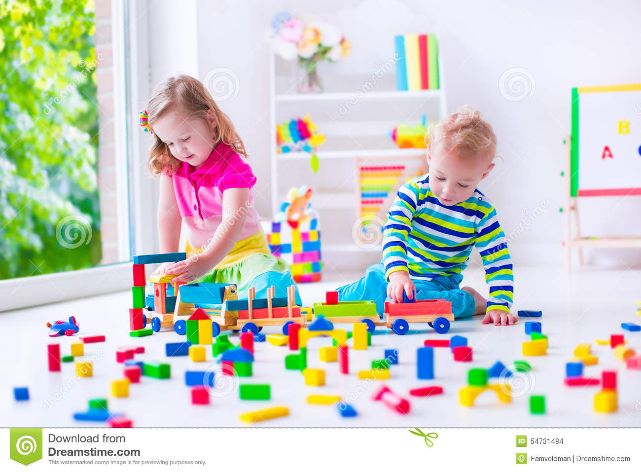 ... . Two toddler children build tower of colorful wooden blocks. Child