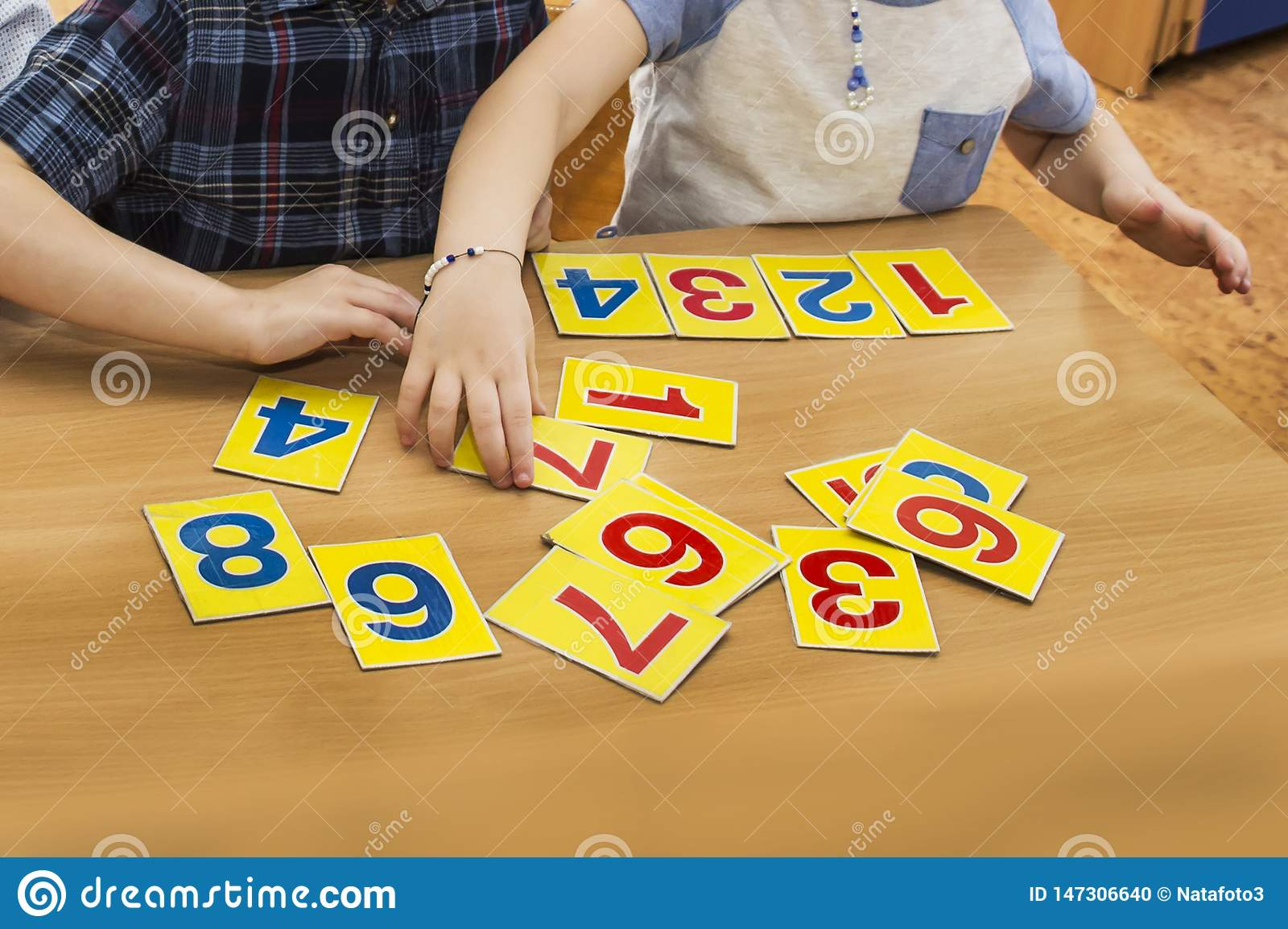 Kids are playing. Educational games. A child in kindergarten. The hands of a child. Maths. Cards for development