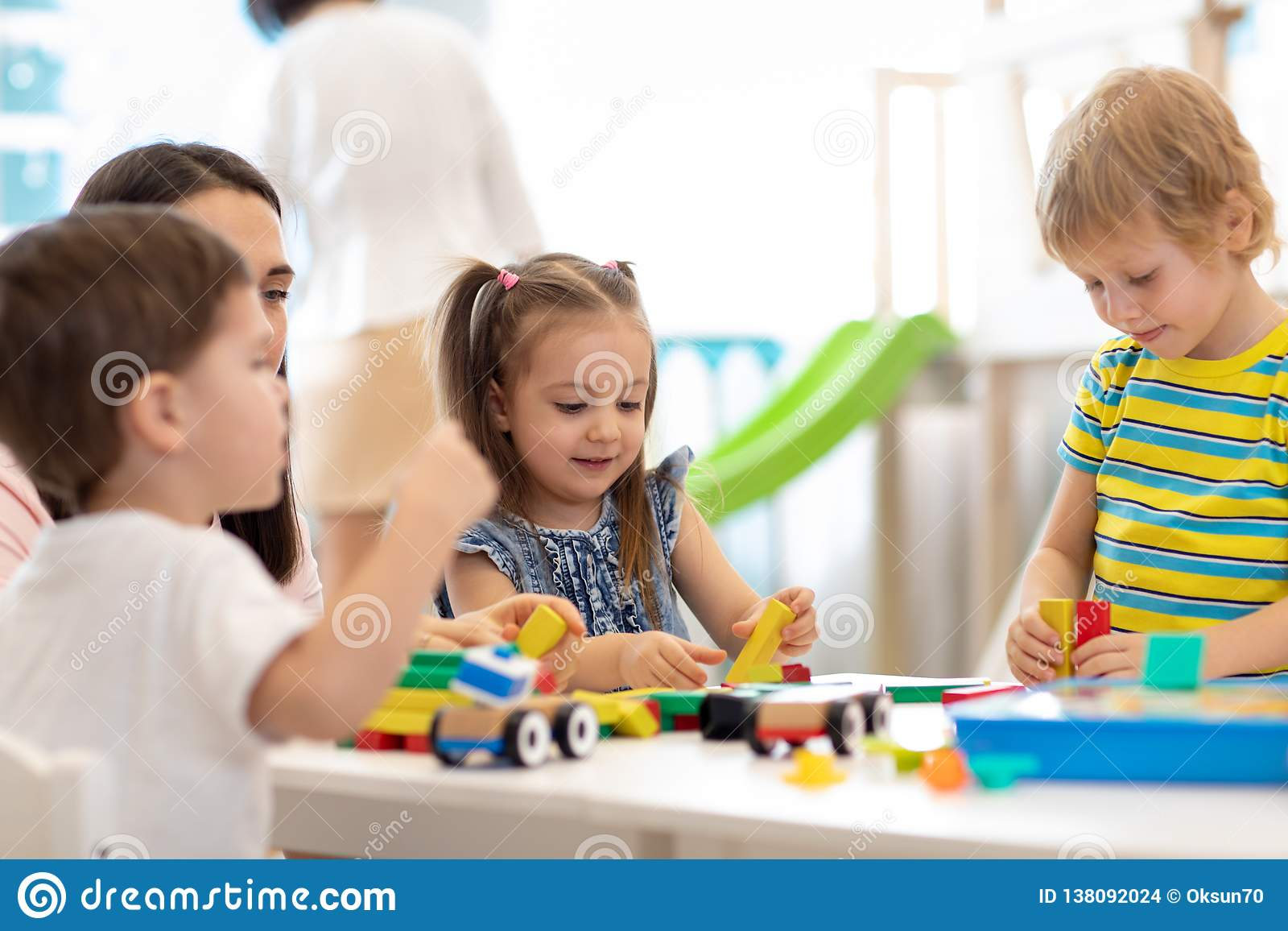 Kids playing with educational toys in kindergarten. Nursery teacher looking after children
