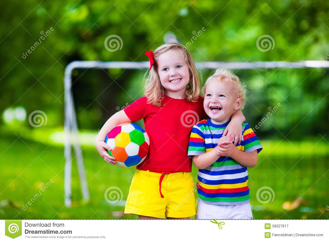 Kinder Garden: Kids Playing Football In A Park Stock Image