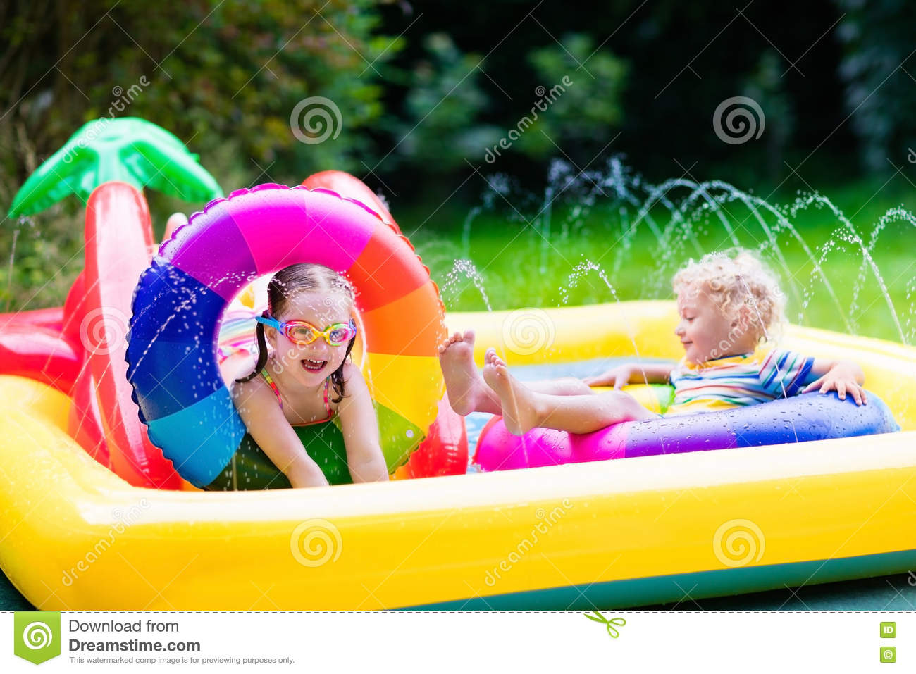 Little boy playing in garden swimming pool stock for Baby garden pool