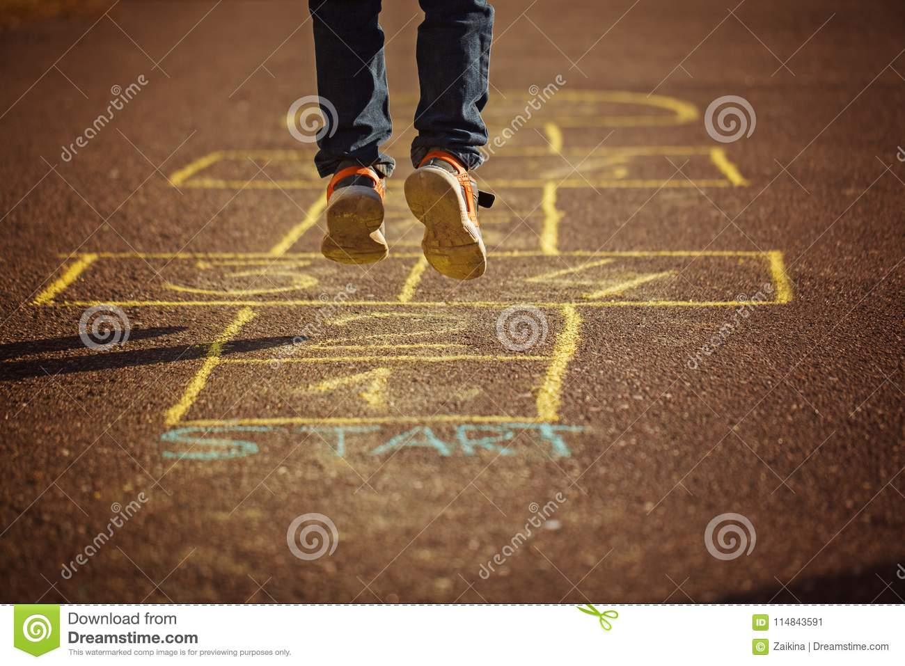Kids playing hopscotch on playground outdoors. Hopscotch popular street game.