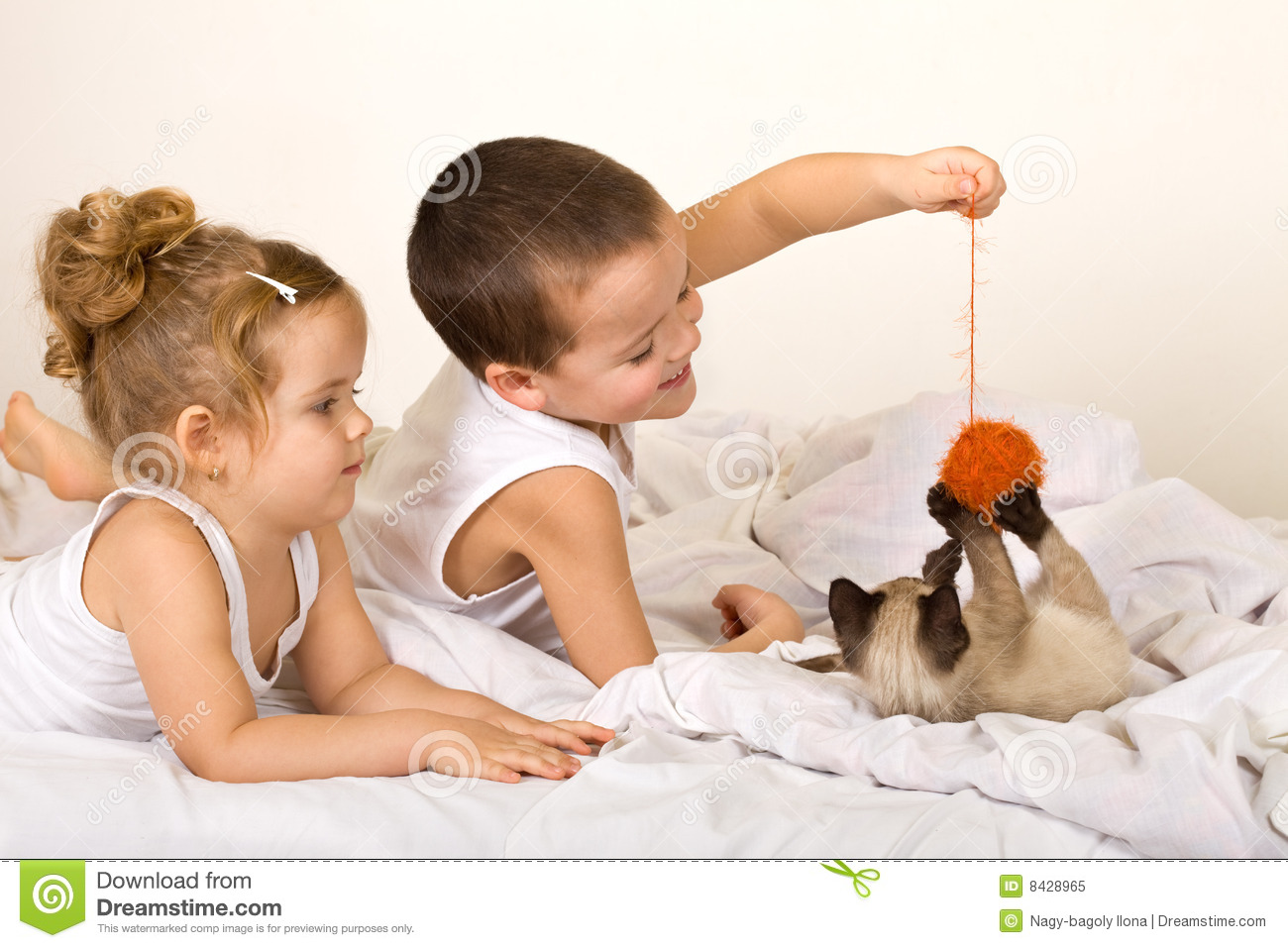 Kids playing with a kitten and a yarn ball