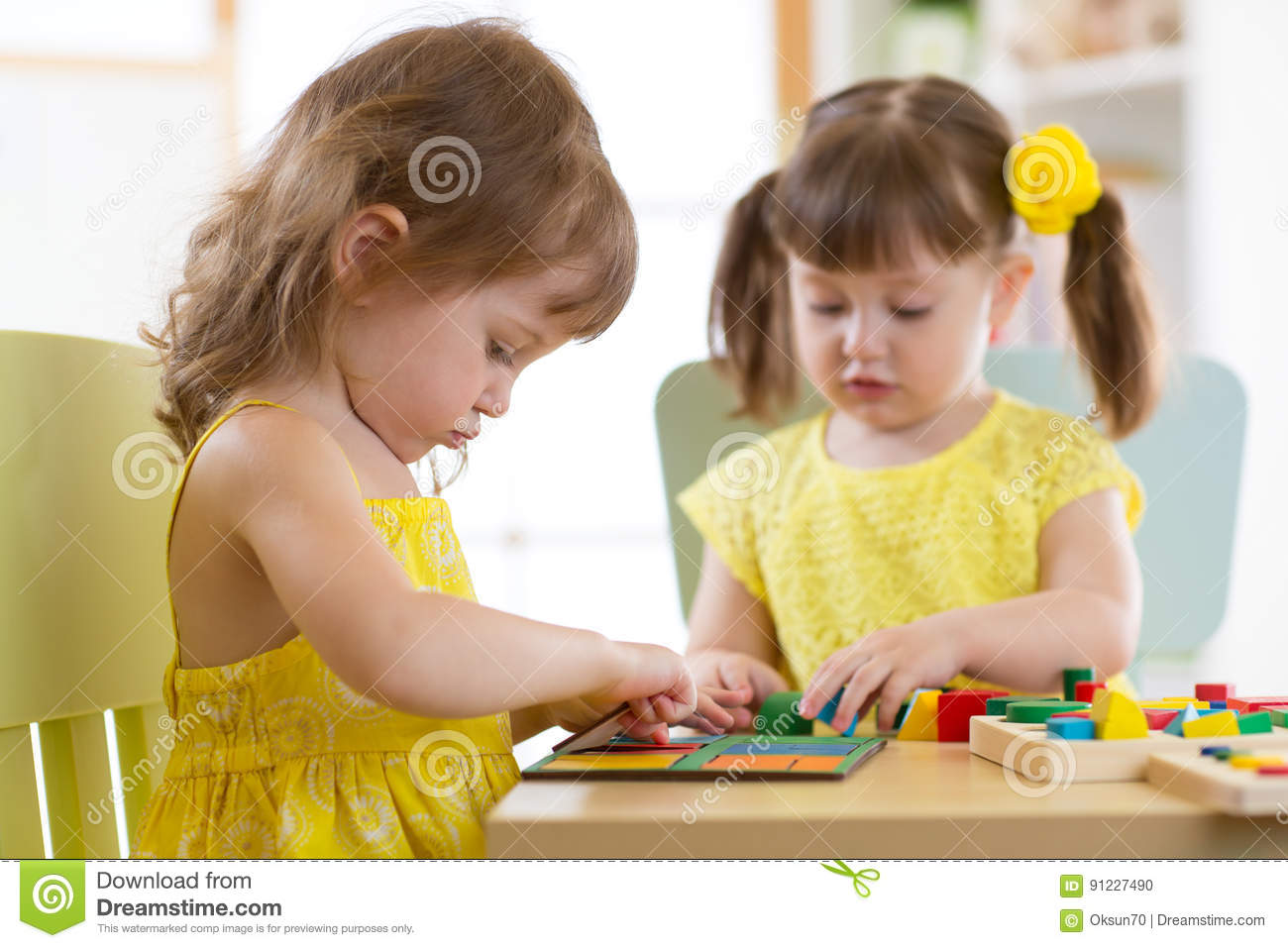 Kinder Garden: Kids Playing With Logical Toy On Desk In Nursery Room Or