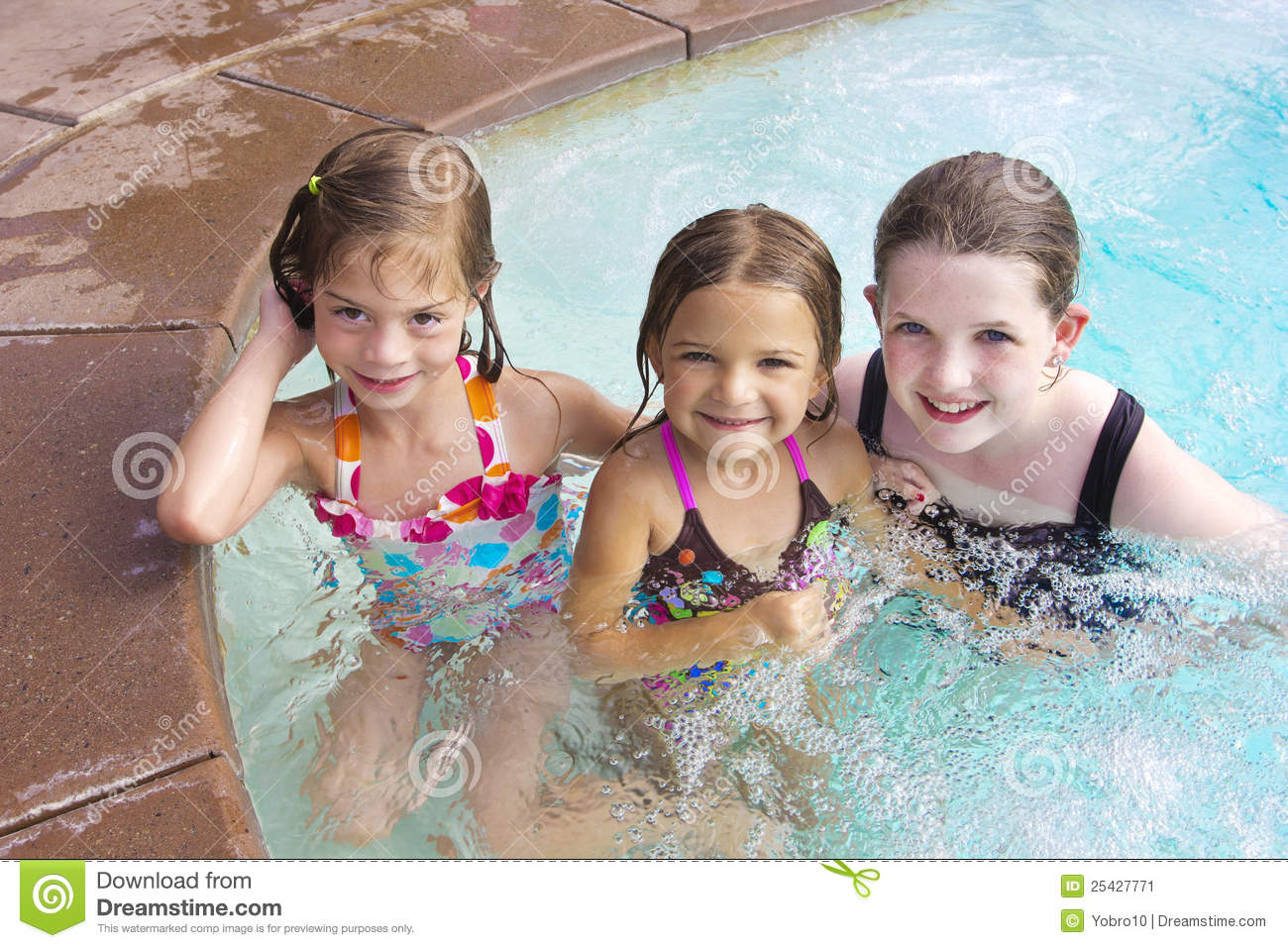 Three cute little girls playing together in the swimming pool on a hot ...