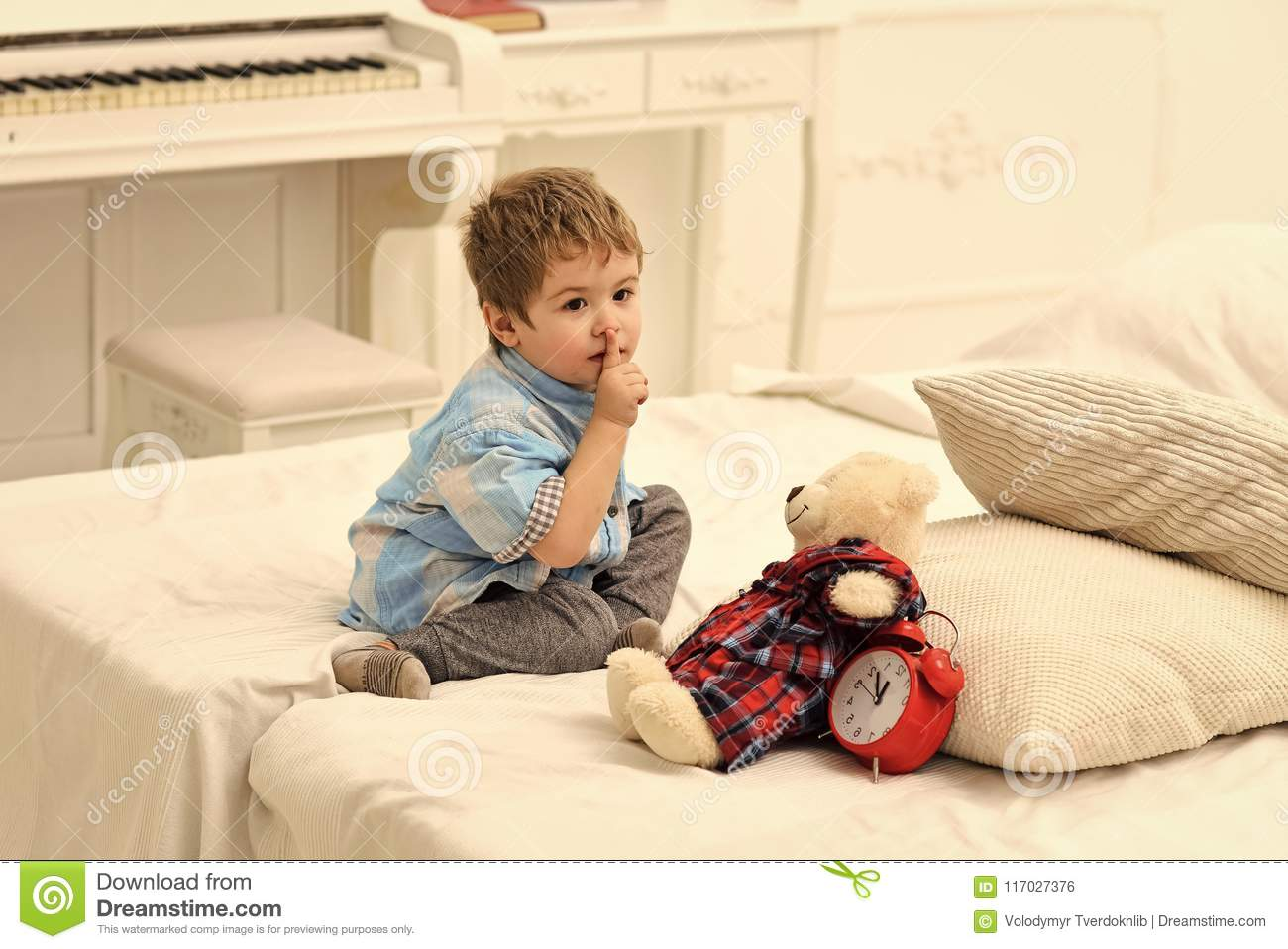 Kids playing with toys. Child in bedroom with silence gesture. Kid put plush bear near pillows and alarm clock, luxury