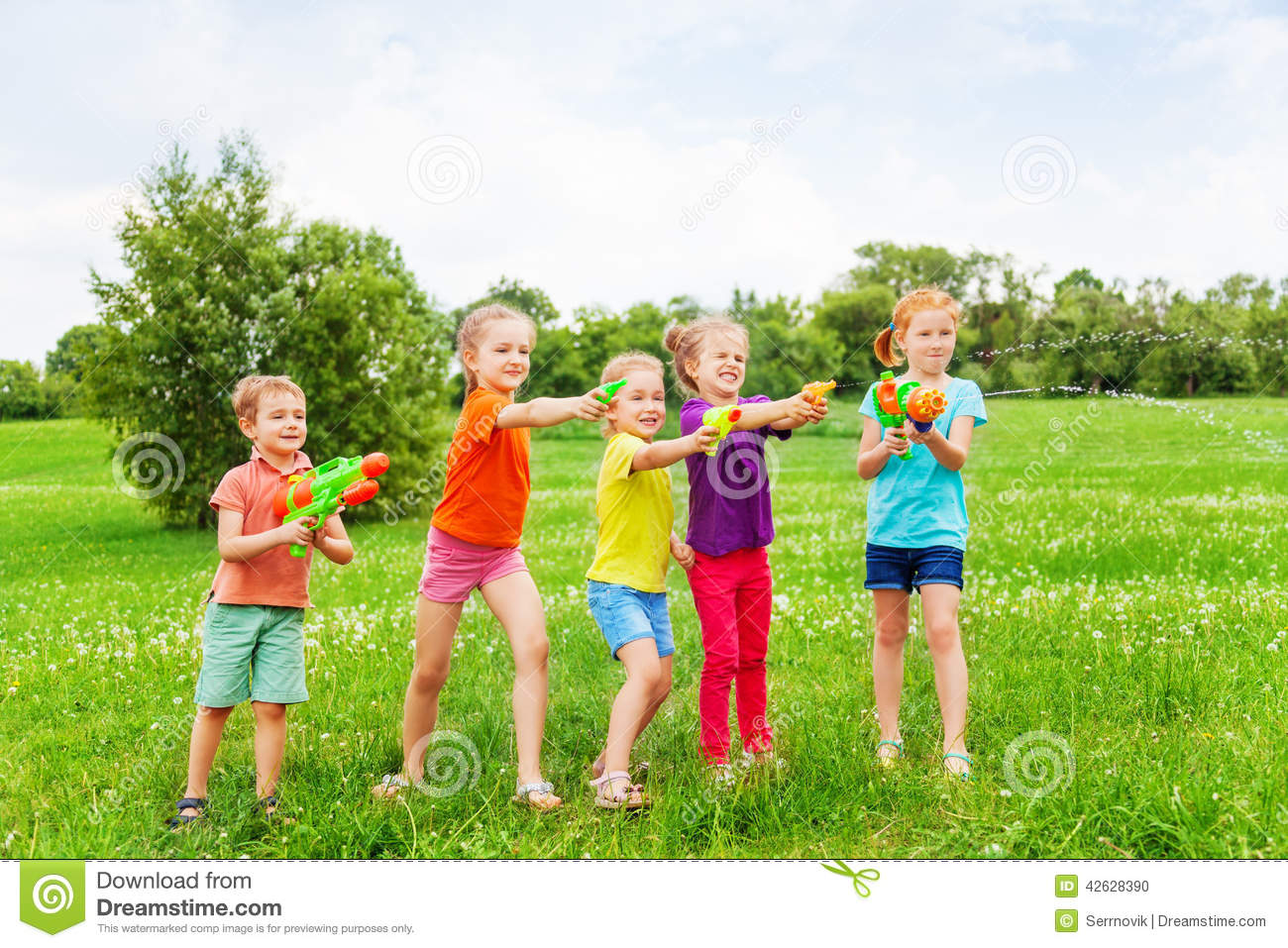 kids play water Kids playing with water guns on a meadow Stock Photo