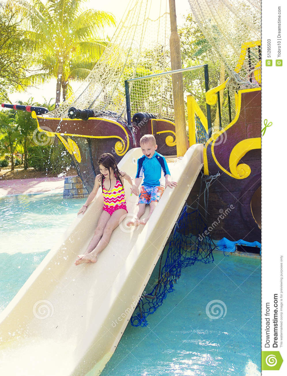 kids playing on a water slide at a waterpark stock photo. Black Bedroom Furniture Sets. Home Design Ideas