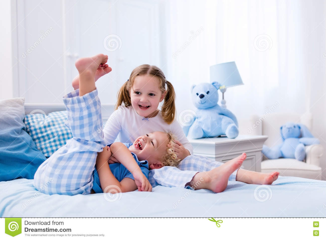 Kids Playing In White Bedroom Stock Photo