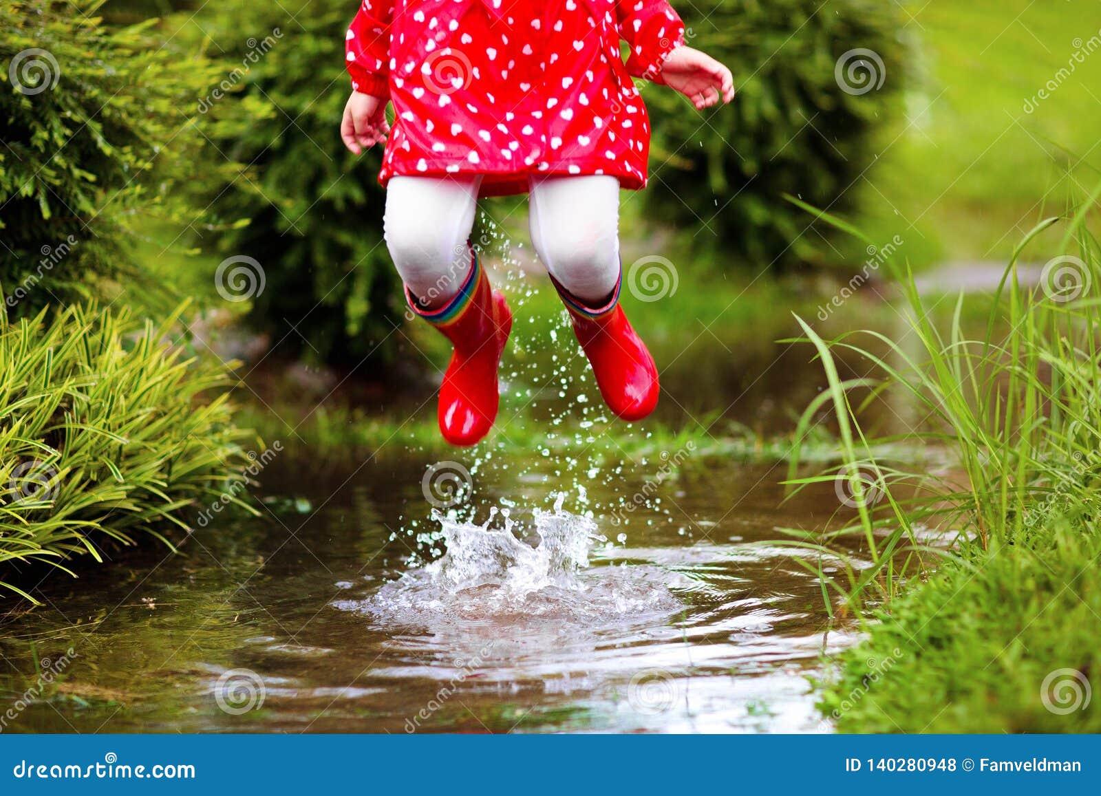 Kids in puddle in autumn rain. Waterproof wear