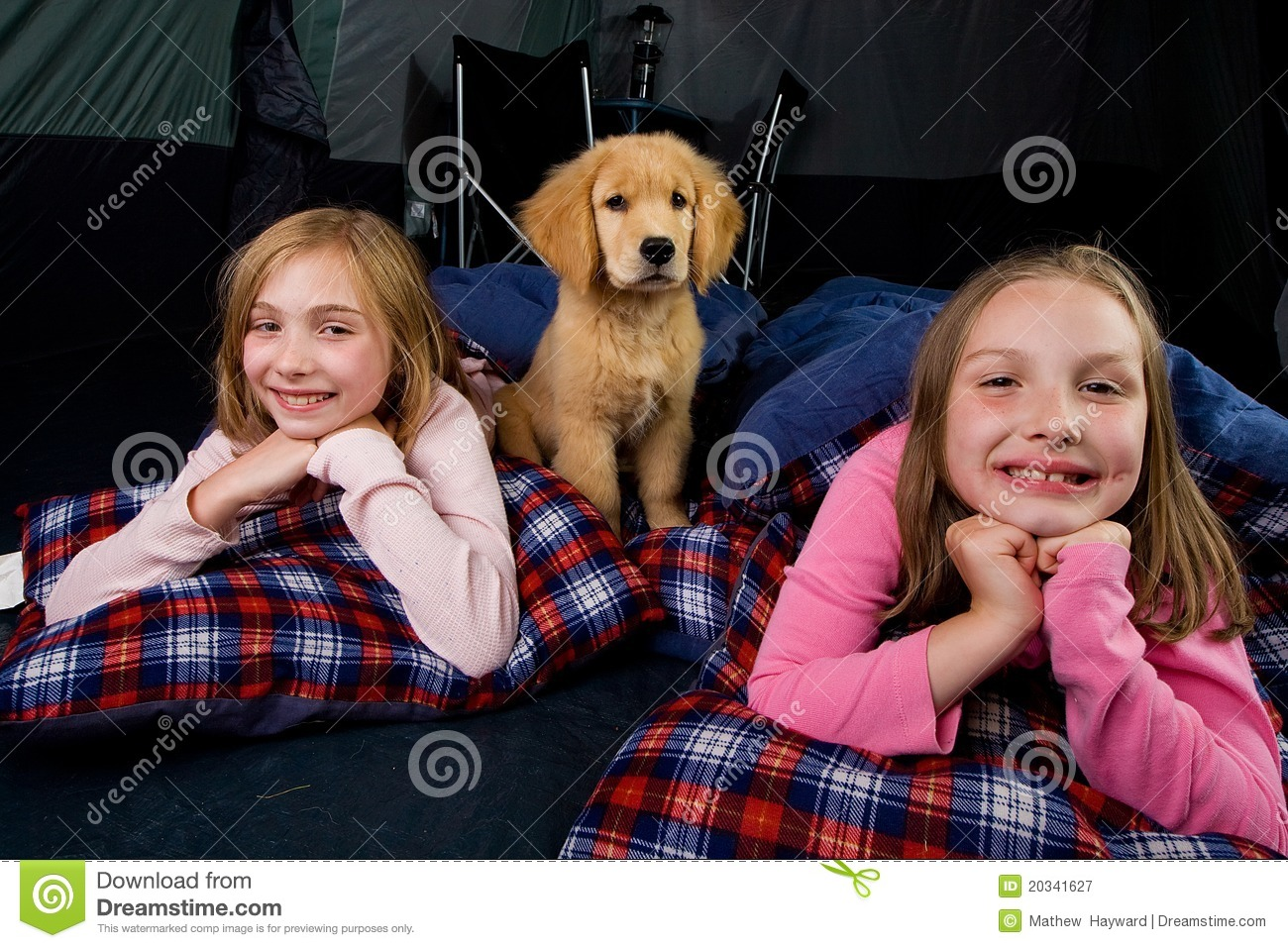 Kids and a puppy camping in a tent